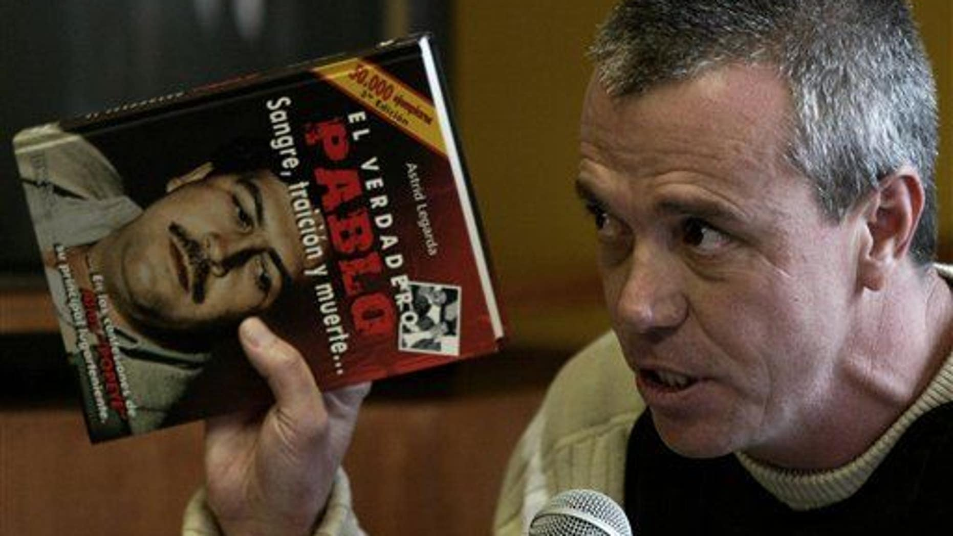 """In this June 27, 2006, photo, Jhon Jairo Velasquez, a former hit man for Pablo Escobar, testifies while holding a book titled """"The True Pablo: Blood, Treason, and Death."""""""