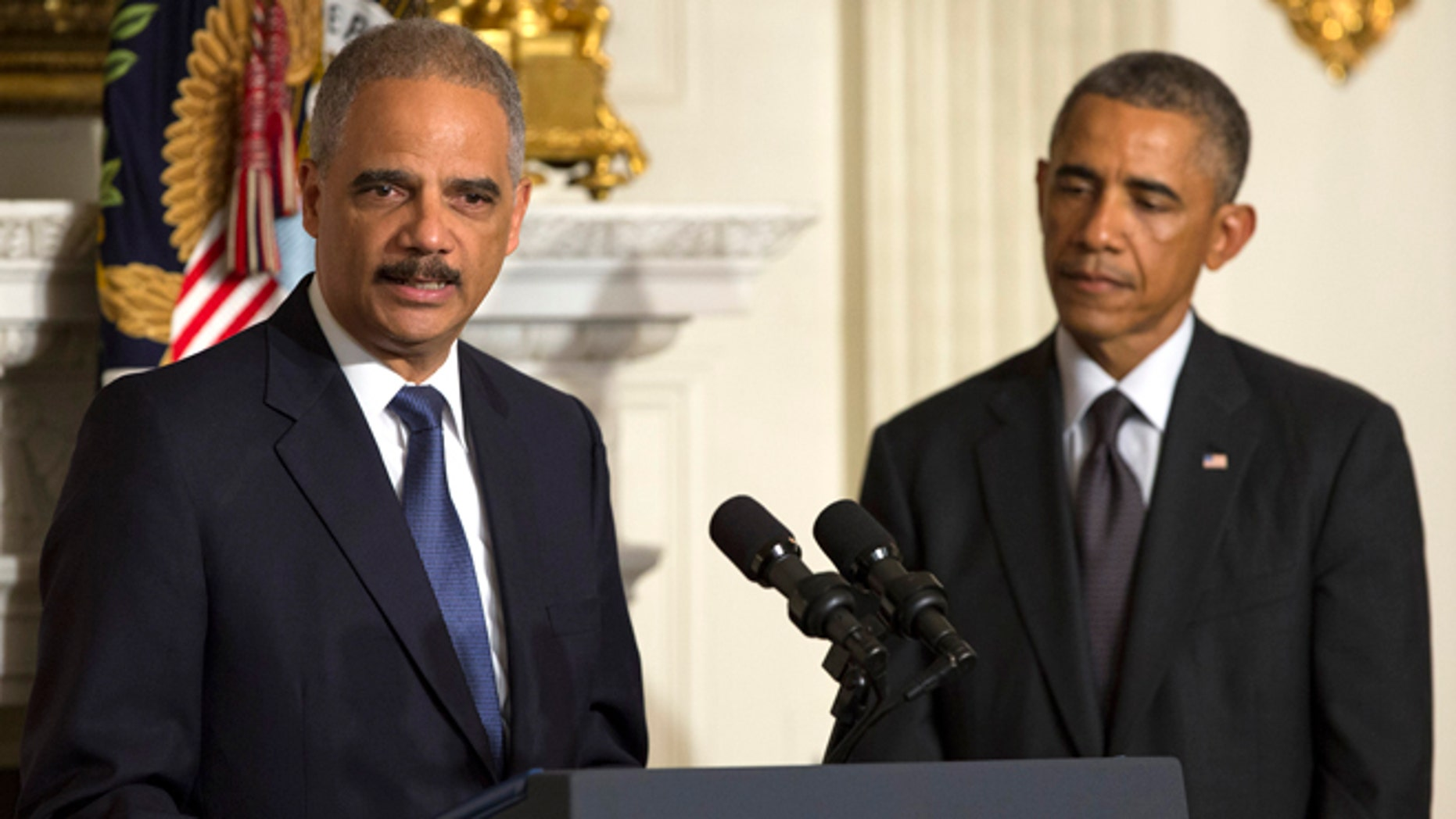 In this Thursday, Sept. 25, 2014 photo, President Barack Obama, right, looks on as Attorney General Eric Holder speaks in the State Dining Room of the White House, in Washington.
