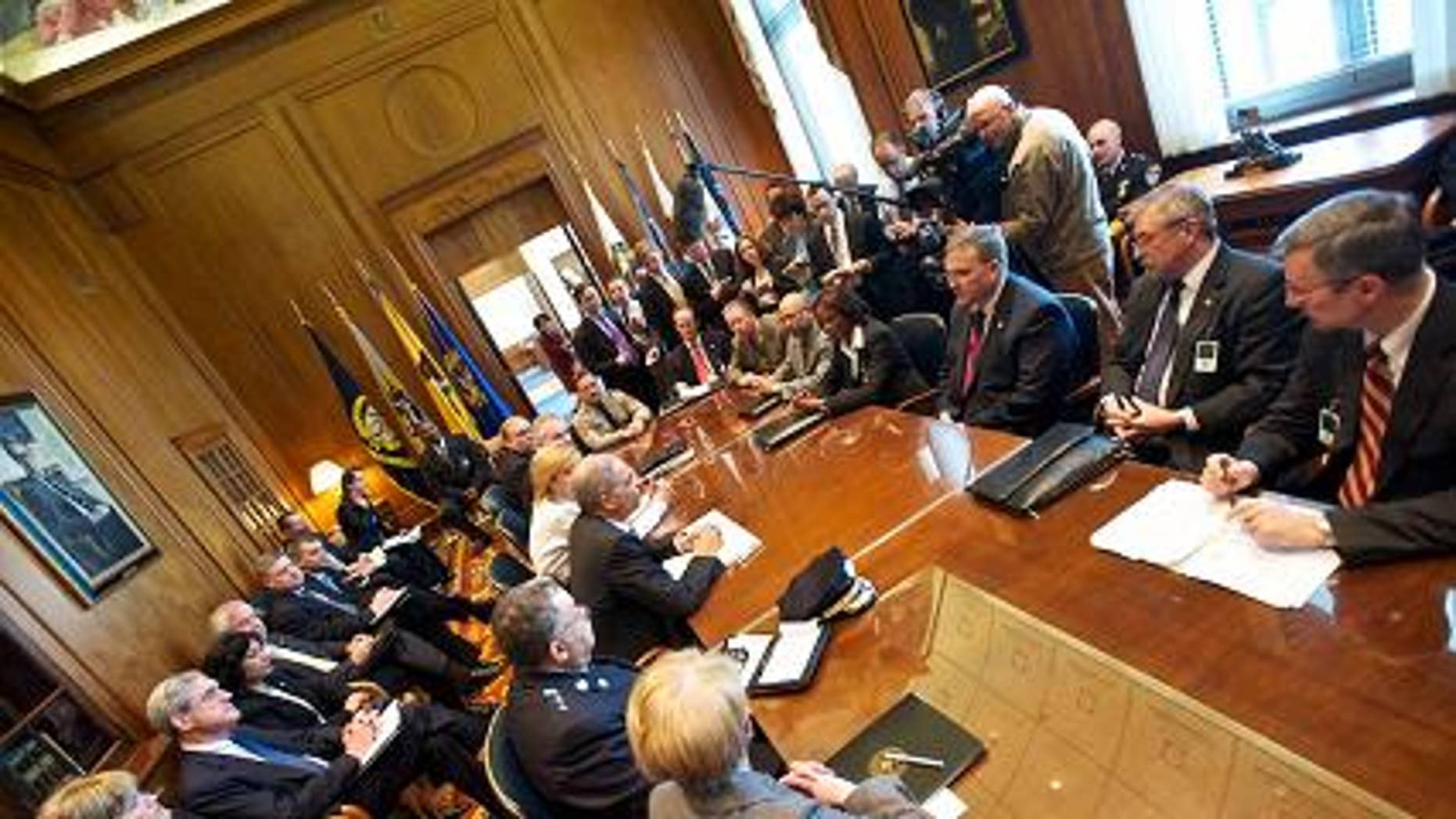 Reporters listen to Attorney General Eric Holder before his meeting with police officials, March 22