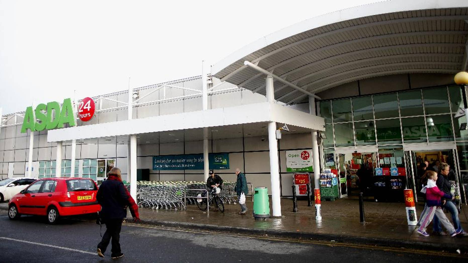 FILE - This is a  Friday, Nov. 29, 2013 file photo of shoppers at the entrance to Asda supermarket store in West Belfast, Northern Ireland after  at least one person was injured and taken to hospital from the store earlier Friday, as shoppers rushed to get their hands on sale deals for their Black Friday event. Halloween and Mother's Day have become staples of the U.K. shopping calendar. Now Black Friday looks as though it may be the next big retail import from the United States. Shopping on the day after Thanksgiving is becoming a thing in Britain, too  even if the country doesn't celebrate Turkey day thanks mainly to the marketing efforts of major retailers. Asda, is owned by U.S. retail giant Walmart, (AP Photo/Peter Morrison, FILE)