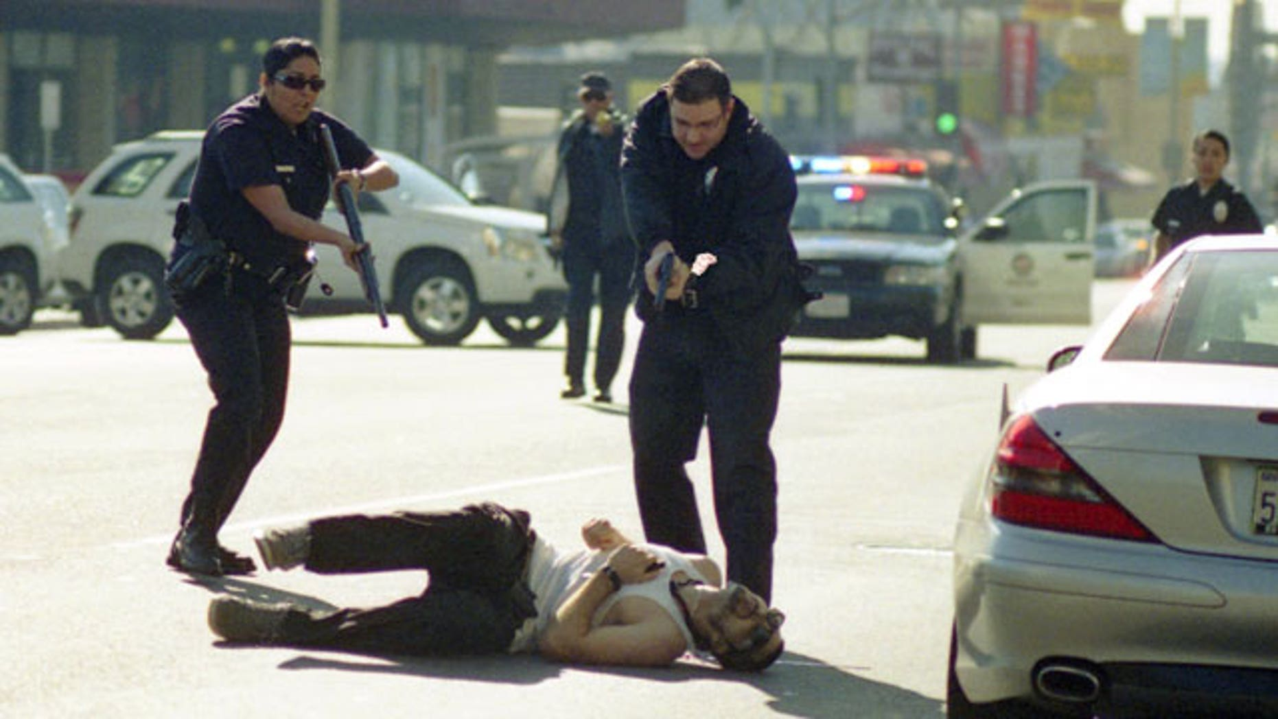 December 9, 2011: This image provided by Gregory Bojorquez shows Los Angeles Police officers advancing on a wounded gunman at sunset and Vine streets in Los Angeles.