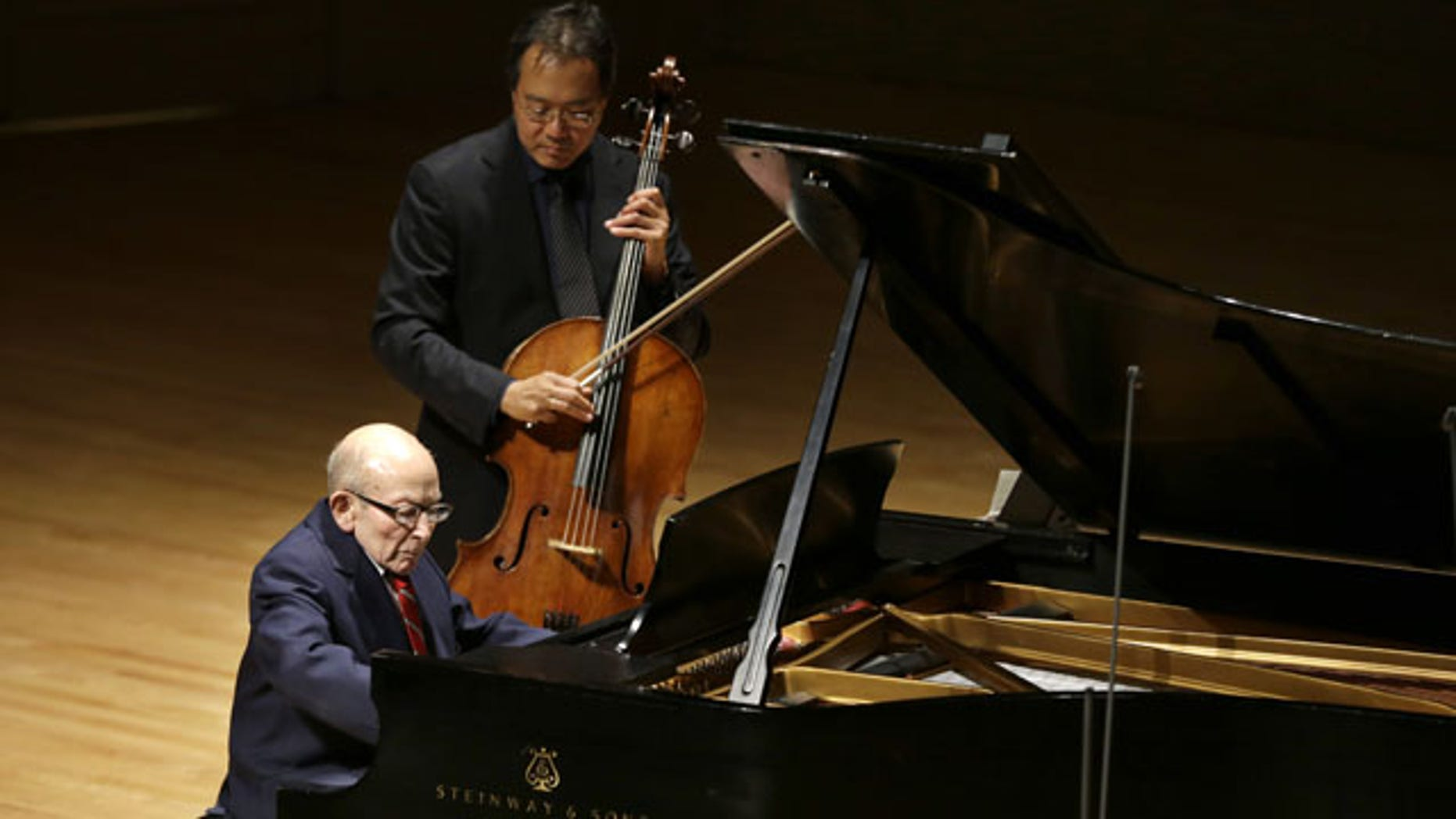 October 22, 2013: Holocaust survivor George Horner, front left, performs with cellist Yo-Yo Ma, top, on stage at Symphony Hall in Boston. The 90-year-old pianist made his orchestral debut with Ma, where they played music composed 70 years ago at the Nazi concentration camp where Horner was imprisoned. (AP Photo/Steven Senne)
