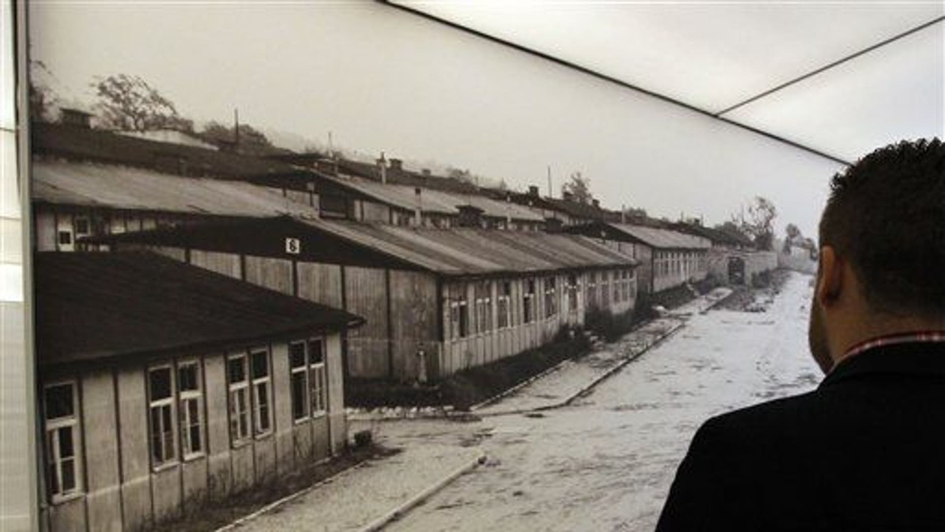 A visitor looks at a poster of the former Nazi concentration camp of Mauthausen during a press preview in a new memorial room in the former camp in Mauthausen, Austria.