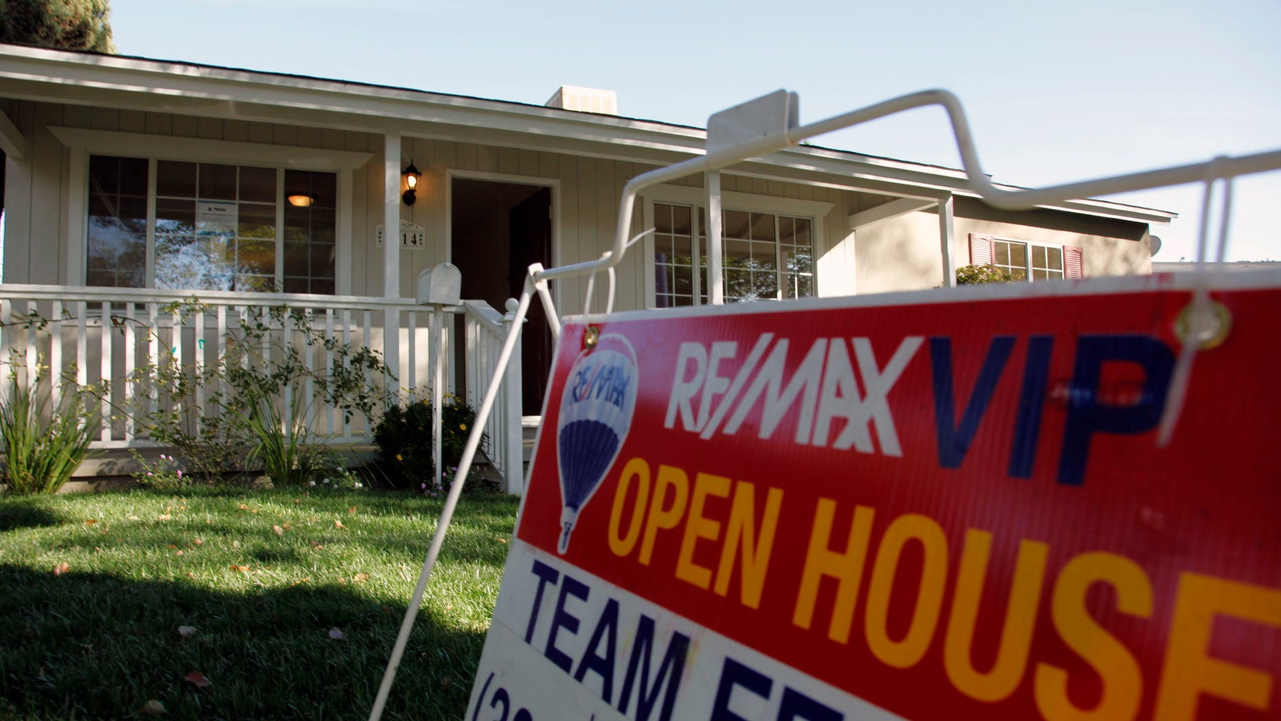 In this Nov. 4, photo, an open house sign is seen on the front lawn of a home for sale in Los Angeles. Home prices are dropping in the nation's largest cities and are expected to fall through next year, with the worst declines coming in areas with high numbers of foreclosures.
