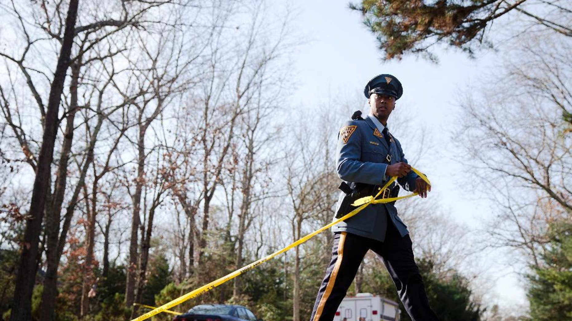 A New Jersey State Police trooper secures a police line at the scene of a shooting, Thursday, Nov. 20, 2014, in Tabernacle, N.J. A shooting at the home in a secluded wooded area of southern New Jersey left two children dead and a woman and another child wounded, state police said Thursday.  (AP Photo/Matt Rourke)