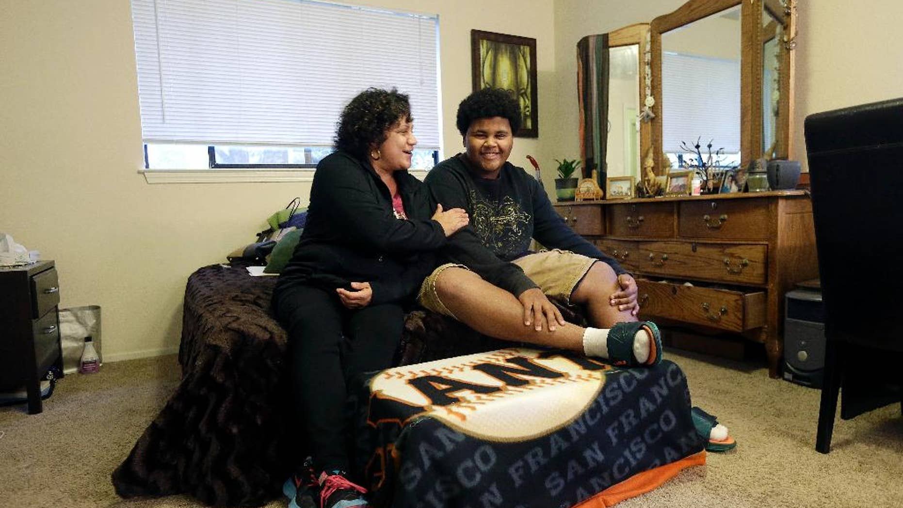 Nov. 13, 2014: In this photo, Gina Cooper, left, and her son Dante Walton, 14, pose for photos at their home in San Carlos, Calif. After a few months as nomads in 2012 when Cooper and Walton, then 12, had to vacate their home when her salary became insufficient to pay the rent, they found shelter and support with an interfaith program and stayed there five months before Cooper saved enough to be able to afford housing on her own.