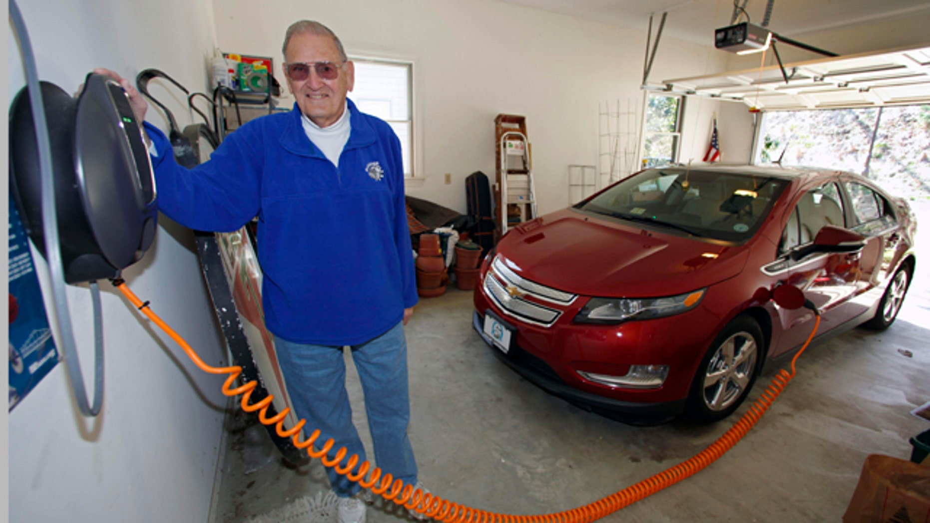 "This Friday, March 25, 2011 photo shows James Brazell as he poses with a charging unit for his Chevy Volt electric car at his home in Asheville, N.C. Brazell plugs the car in after short trips. ""Pretty much I top it up every time I bring it into the garage,"" he said.    (AP Photo/Chuck Burton)"