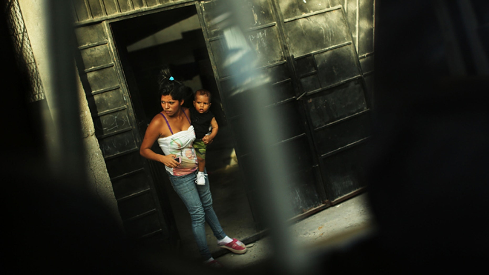 TEGUCIGALPA, HONDURAS - JULY 20: A woman and her son look out of a doorway in a neighborhood with heavy gang violence on July 20, 2012 in Tegucigalpa, Honduras. Honduras now has the highest per capita murder rate in the world and its capital city, Tegucigalpa, is plagued by violence, poverty, homelessness and sexual assaults. With an estimated 80% of the cocaine entering the United States now being trans-shipped through Honduras, the violence on the streets is a spillover from the ramped rise in narco-trafficking.  (Photo by Spencer Platt/Getty Images)