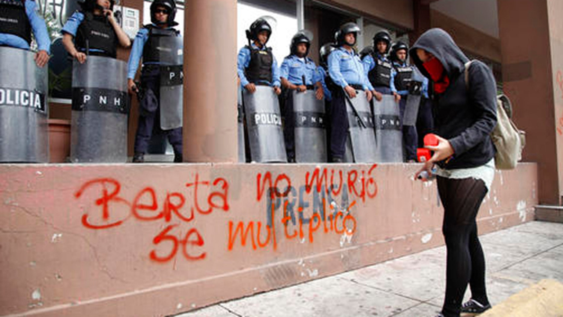 "A protester writes with spray paint ""Berta did not die, she multiplied"" in front of riot police guarding the attorney general's office in Tegucigalpa, Honduras, Thursday, Oct. 20, 2016. Members of the Civic Council of Popular and Indigenous Organizations of Honduras (COPINH) and people belonging to the Garifuna people protested to demand justice over the March 2016 murder of Honduran indigenous leader and environmentalist Berta Caceres and to halt construction of the Agua Zarca dam, which would displace many of the indigenous Lenca people. (AP Photo/Fernando Antonio)"