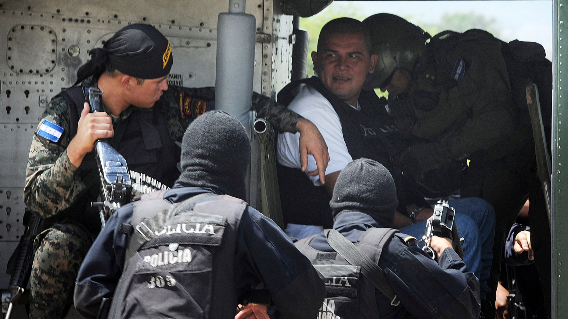 In this Monday, Oct. 10, 2011 photo, alleged drug trafficker Mario Ponce Rodriguez from Guatemala is escorted by police and army personnel during his extradition to the U.S. from Tegucigalpa, Honduras. Honduras has become a main transit route for South American cocaine, a trend that has helped drive the country's homicide rate to the highest level in the world and left many villages dependent on the cocaine trade. (AP Photo/Fernando Antonio)