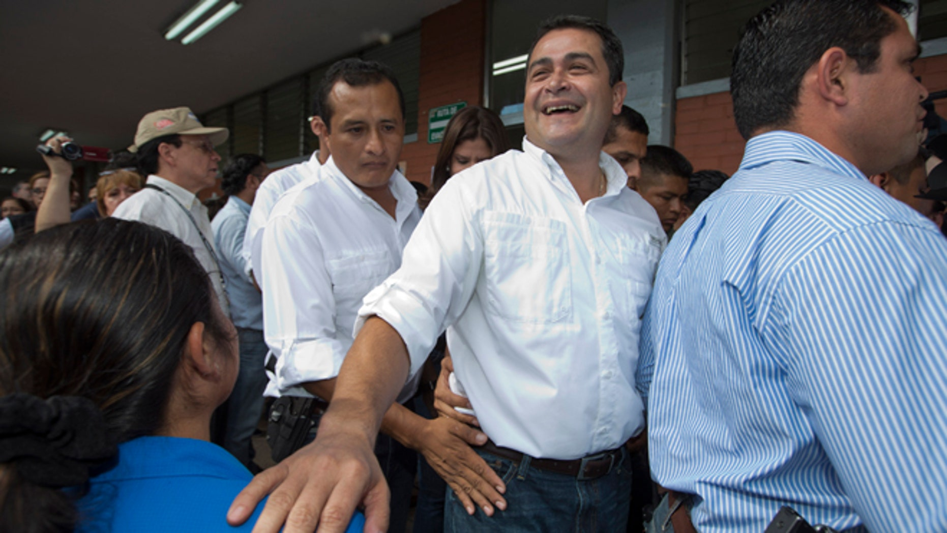 FILE - In this Nov. 24, 2013, file photo, then National Party Presidential Candidate Juan Orlando Hernandez, second from right, greets supporters at a polling station in Tegucigalpa, Honduras. Now as President of Honduras, Hernandez has acknowledged Wednesday, June 3, 2015, that his election campaign received financing from businesspeople linked to a social security embezzlement and graft scandal that has sparked large protests, but denied any personal involvement. (AP Photo/Moises Castillo, File)