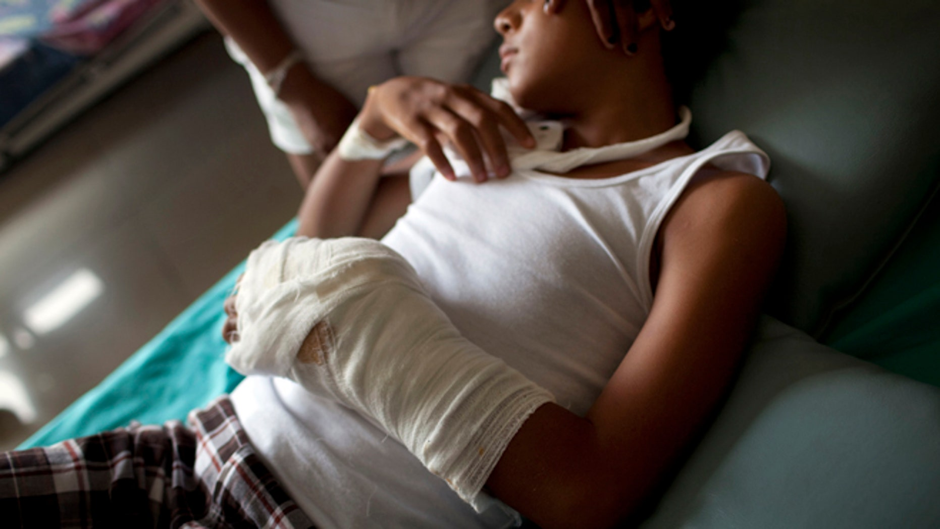 May 20: Wilmer Lucas Walter, 14,  rests while recovering in a public hospital from the wounds caused during an attack involving U.S. helicopters in a DEA-supported anti-drug crackdown by Honduras policein Las Mosquitia region, in La Ceiba, Honduras.  AP Photo/Rodrigo Abd)