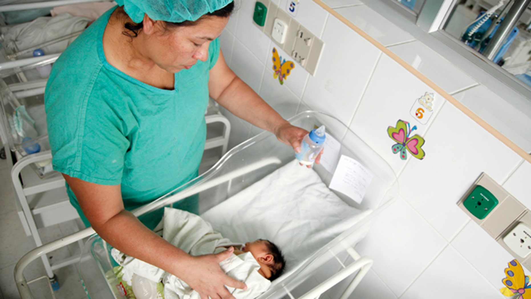 A nurse bottle feeds a newborn baby aflicted with microcephaly at a maternity ward of the University Hospital in Tegucigalpa, Honduras, Tuesday, July 26, 2016. Honduras' health minister, Dr. Yolani Batres, says eight babies with severe birth defects linked to the Zika virus have been born in the Central American country. Some women who contract Zika during their pregnancies have given birth to babies with microcephaly, which leads to babies with abnormally small heads and improperly developed brains. (AP Photo/Fernando Antonio)