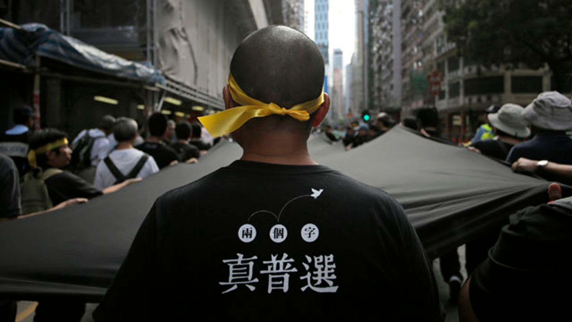 September 14, 2014: A protester stretches out a 500 meter long black cloth during a rally in a downtown street in Hong Kong.  The Chinese words on the T-shirt read 'Real Universal Suffrage'. (AP Photo/Vincent Yu)