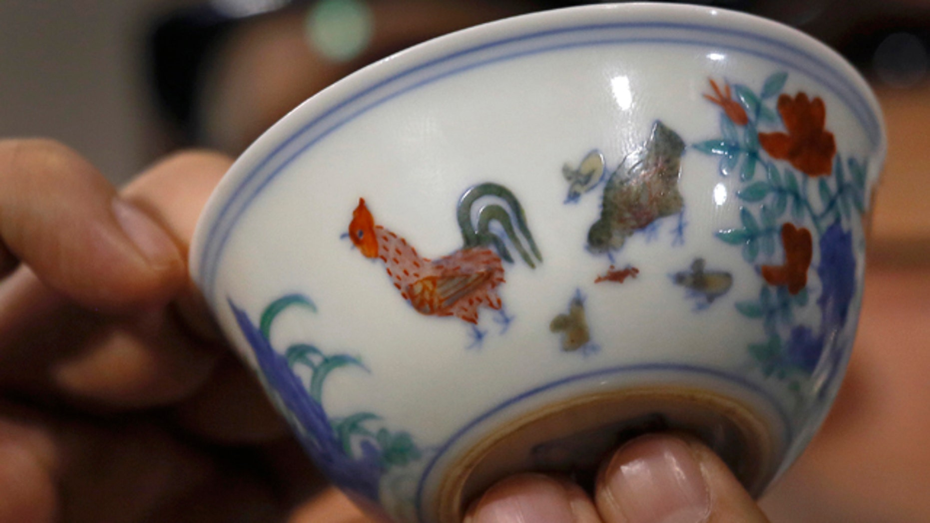 April 8, 2014: The Meiyintang Chicken Cup from the Chinese Ming Dynasty (1368-1644) is displayed during a press conference in Hong Kong. Sothebys said Shanghai collector Liu Yiqian won the bidding for the Chicken Cup, which is decorated with a rooster, hen and their chicks. Including the auction house's commission, the price for the small cup comes to $36.1 million, which Sothebys said is a world record price for Chinese porcelain. (AP Photo/Vincent Yu)