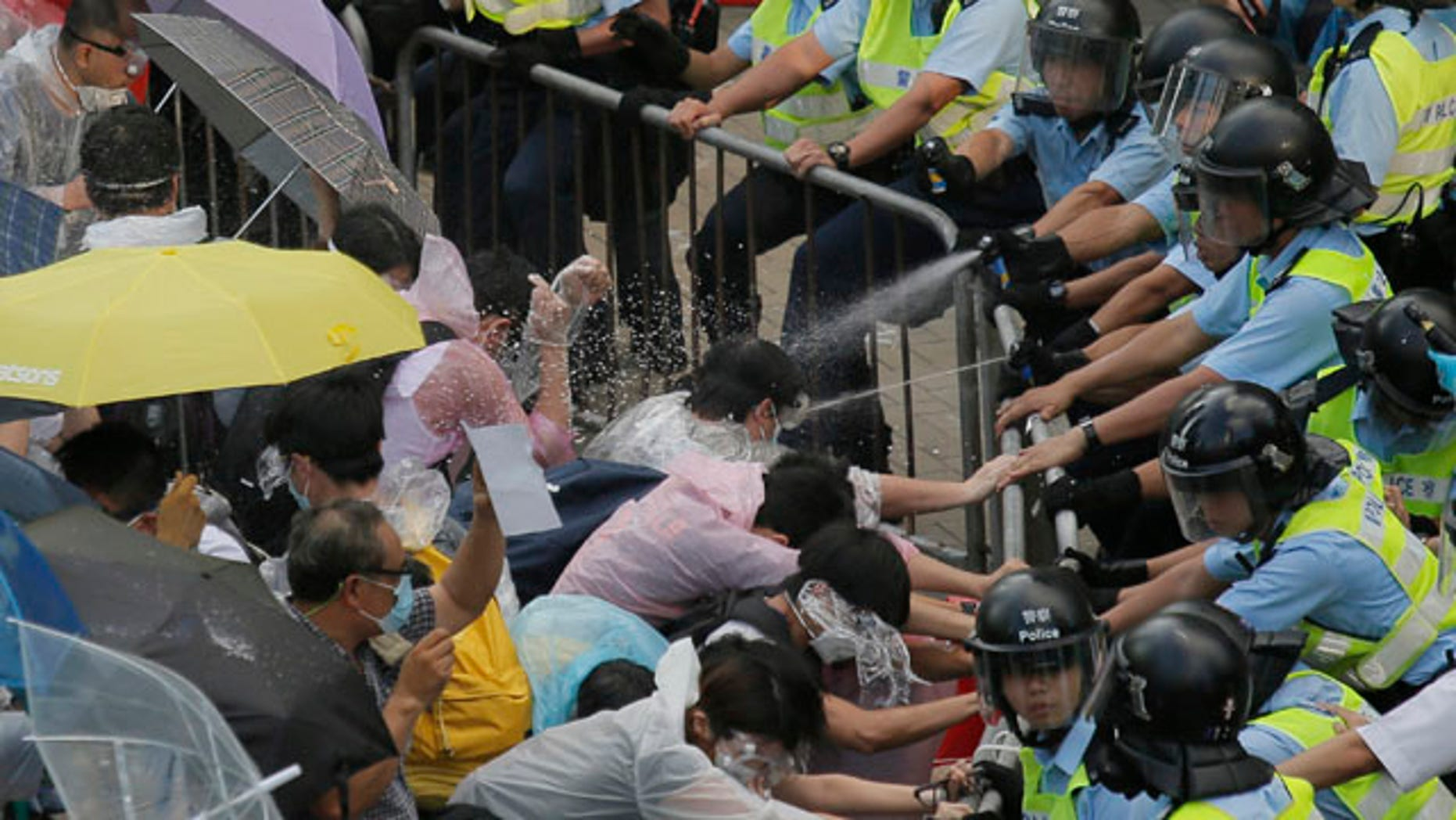 September 28, 2014: Riot police use pepper spray against protesters after thousands of people block a main road to the financial central district outside the government headquarters in Hong Kong. (AP Photo/Vincent Yu)