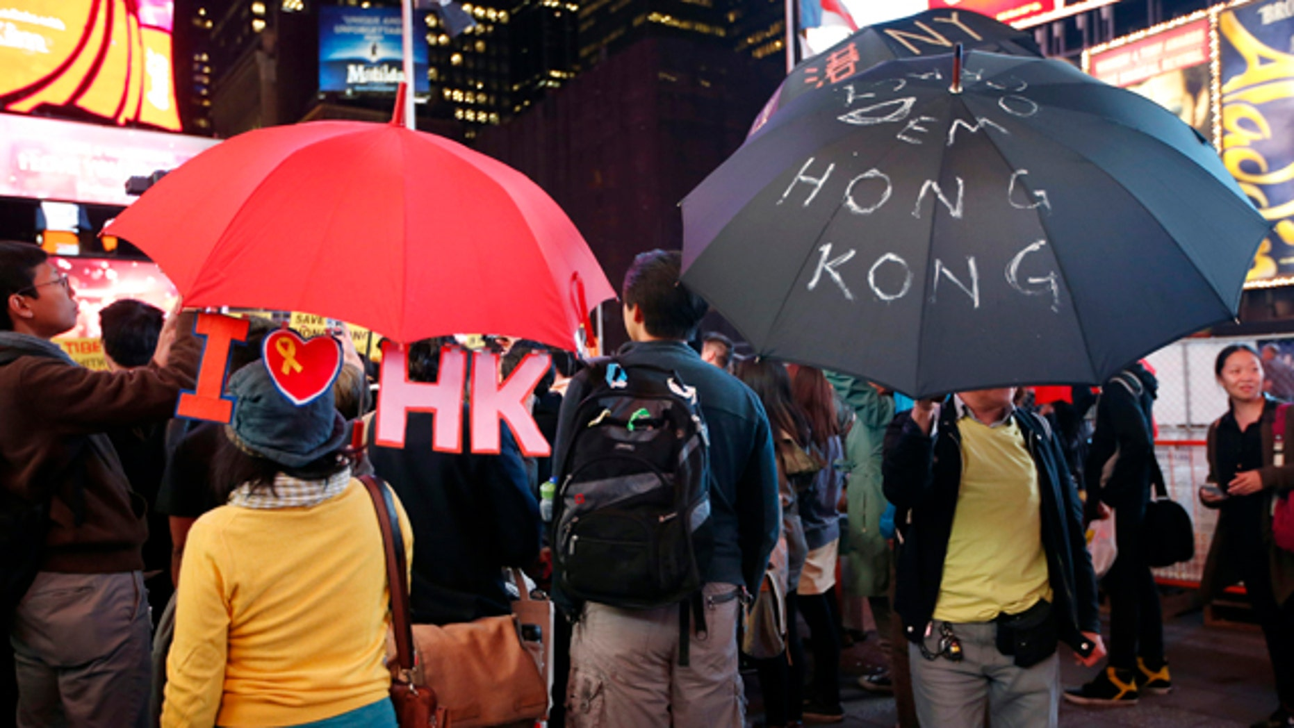 October 1, 2014: People hold up customized umbrellas during a rally in New York's Times Square. Students bearing umbrellas as a sign of solidarity gathered at rallies in several U.S. cities to show support for pro-democracy protesters in Hong Kong. (AP Photo/Kathy Willens)