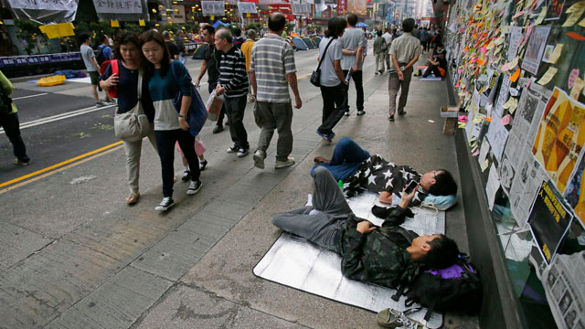 October 16, 2014: Pedestrians walk past sleeping pro-democracy students on an occupied street by the protesters in the Mong Kok district of Hong Kong. (AP Photo/Wally Santana)
