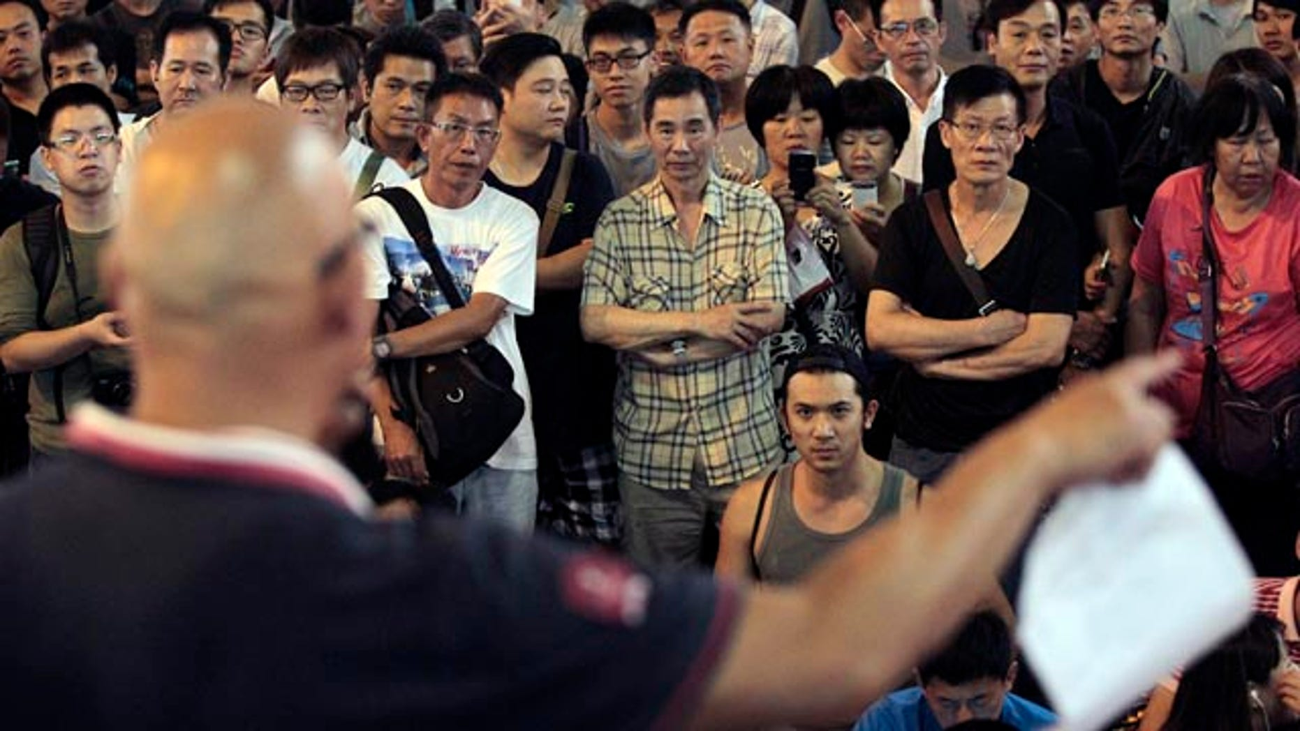 October 20, 2014: Passers by stop and listen to speeches by protest leaders at the pro-democracy protest site in the Mong Kok district of Hong Kong. (AP Photo/Wally Santana)
