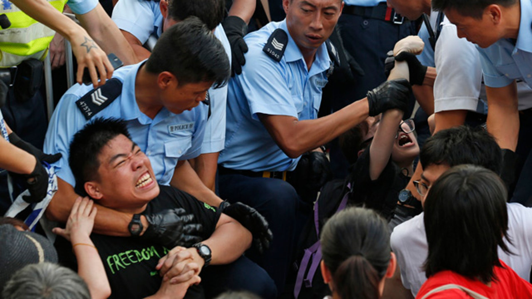 July 2, 2014: Protesters are taken away by police officers after staging a peaceful sit-in overnight on a street in the financial district in Hong Kong. (AP Photo/Kin Cheung)