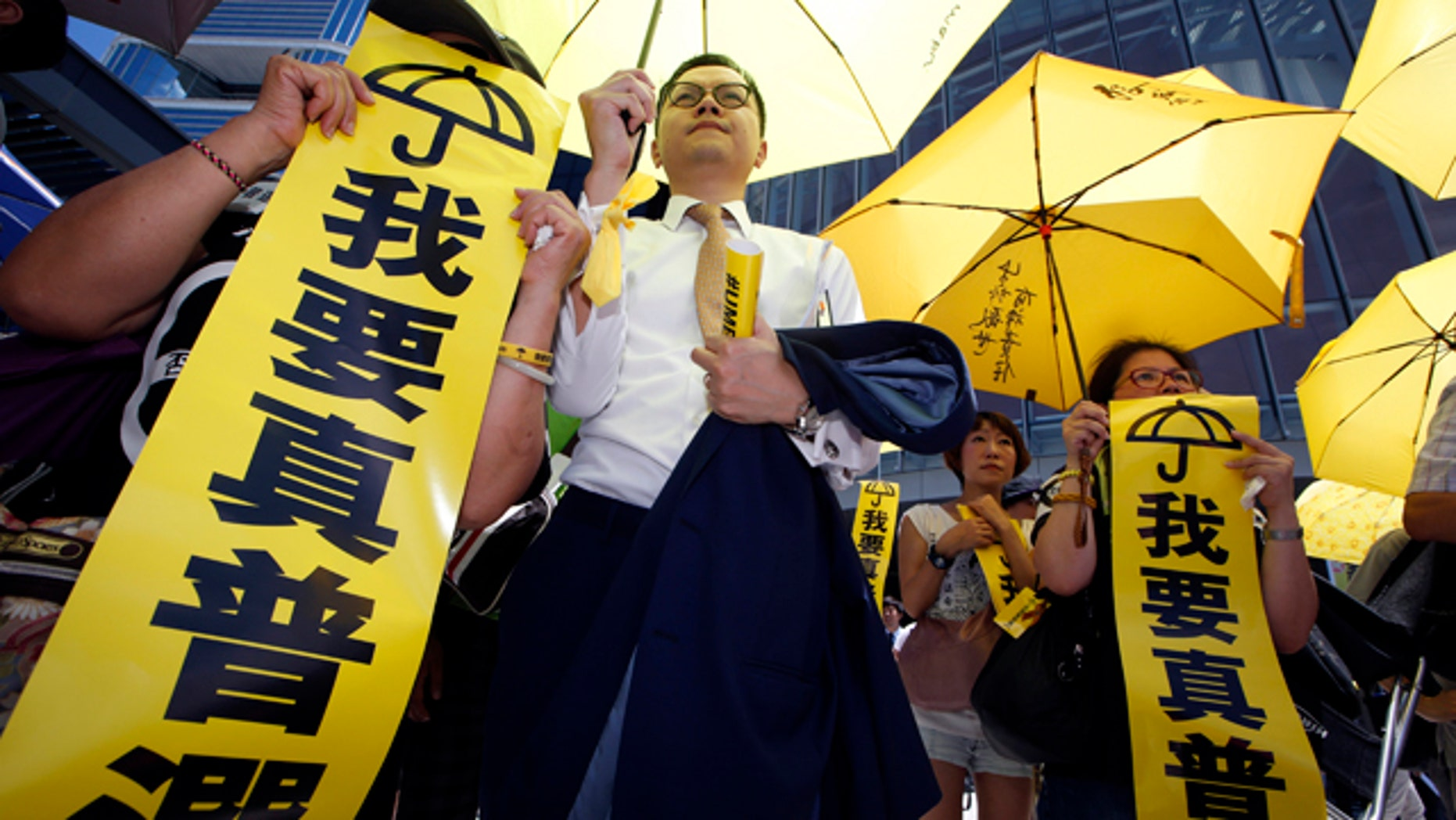 June 18, 2015: Pro-democracy protesters display placards reading I want genuine universal suffrage outside the Legislative Council in Hong Kong. The Hong Kong government's controversial Beijing-backed election reforms were defeated Thursday by pro-democracy lawmakers. (AP Photo/Kin Cheung)