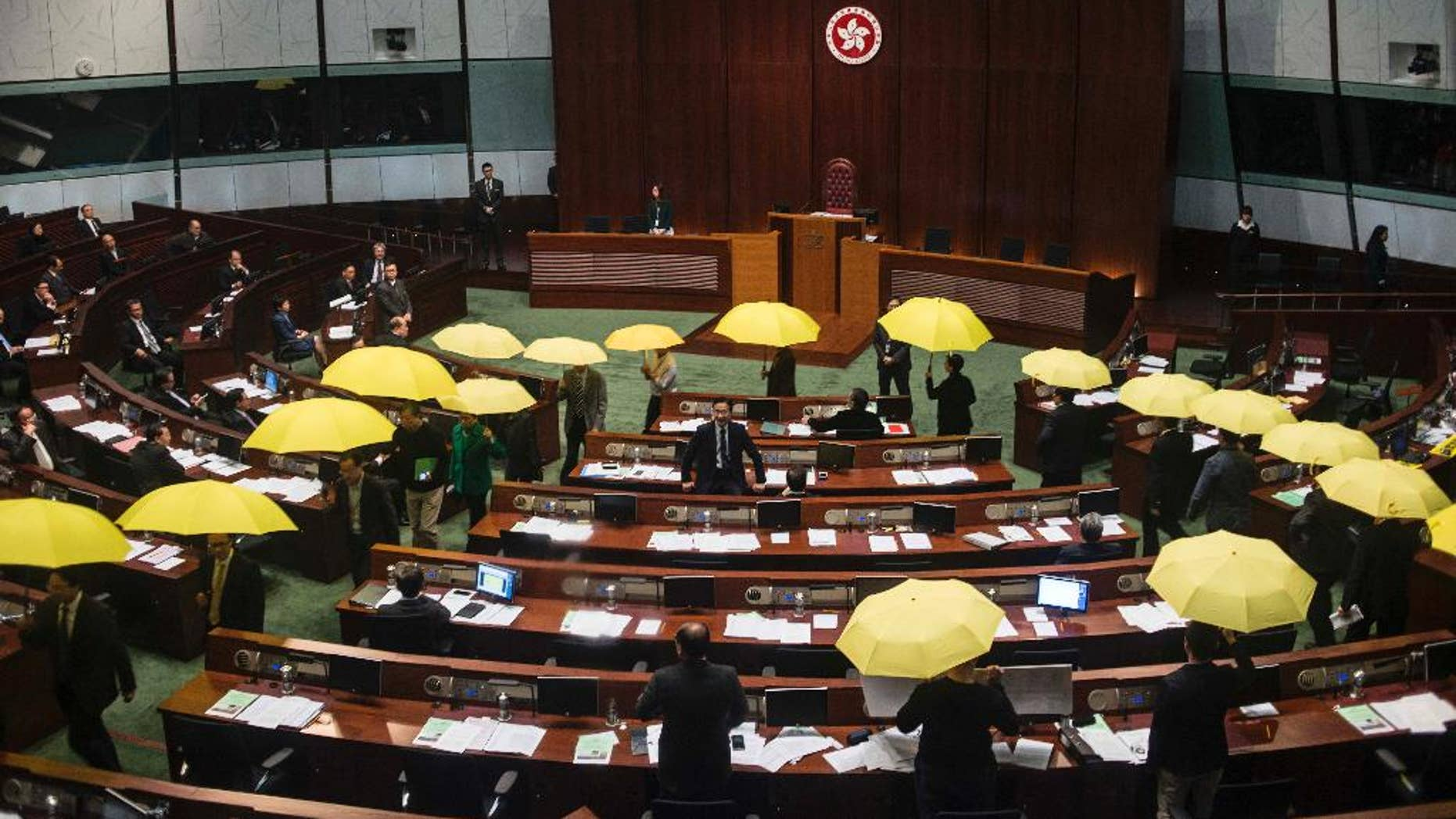 Pro-democracy legislators holding yellow umbrellas walk out of the  Legislative chamber to show their protest in Hong Kong, Wednesday, Jan. 7, 2014. Pro-democracy legislators walked out of the chamber Wednesday to protest the government's intention to stick with a proposal to screen candidates for the city's top executive in 2017, an issue that sparked massive street protests throughout the fall. (AP Photo)