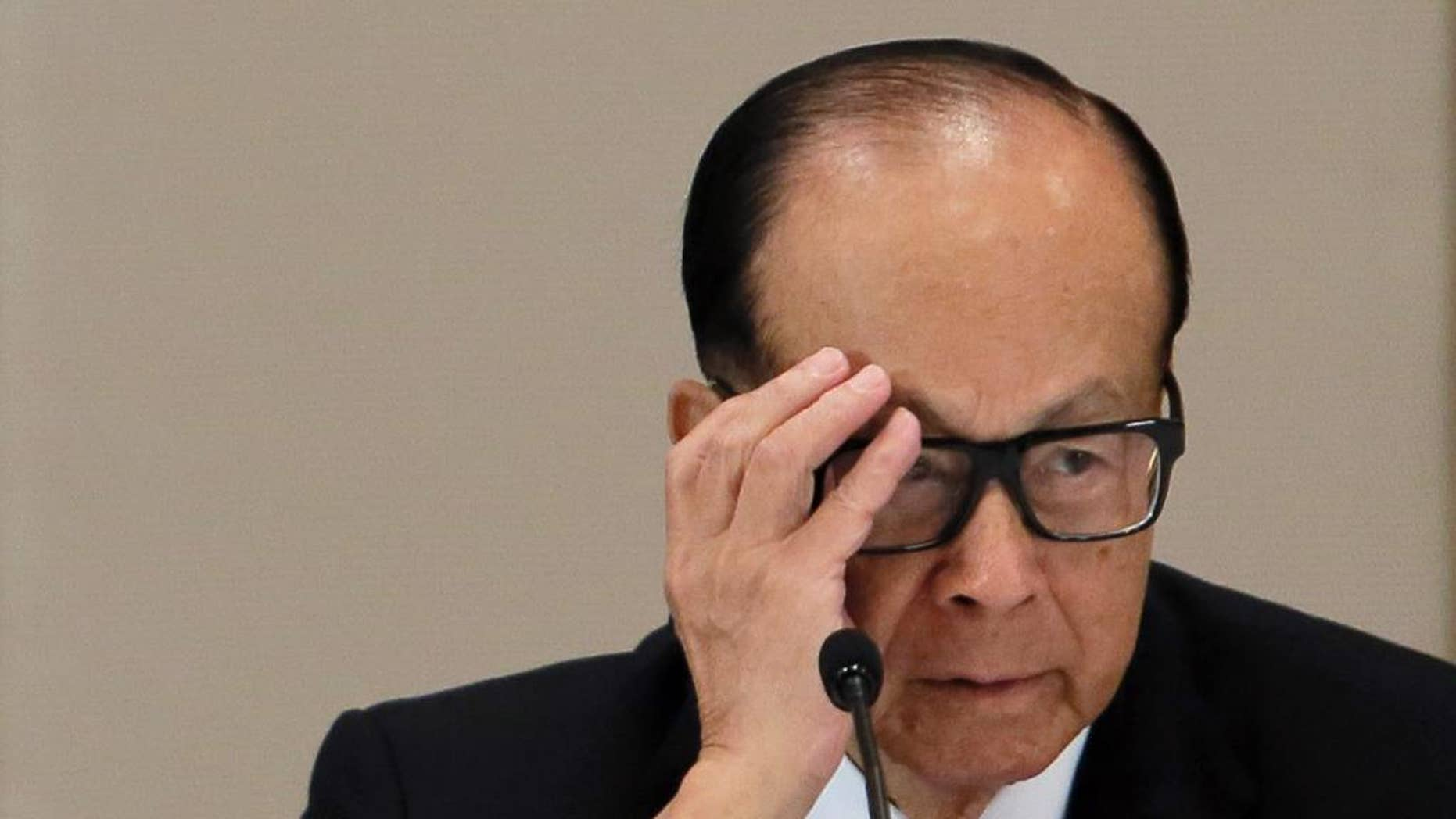 FILE - In this Jan. 9, 2015 file photo, Hong Kong tycoon Li Ka-shing reacts during a press conference in Hong Kong. Hong Kong billionaire Li has defended his business strategy against criticism in China's state media that accused him of abandoning the country because of its slowing growth.(AP Photo/Vincent Yu)