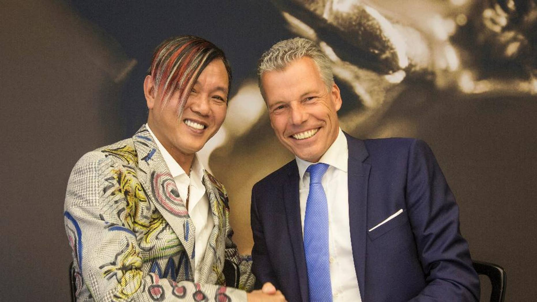 In this Tuesday, Sept. 16, 2014 photo provided by Rolls-Royce Motor Cars, Louis XIII Holdings Ltd. Chairman Stephen Hung, left, poses with Rolls-Royce Motor Cars CEO Torsten Mueller-Oetvoes at the Rolls-Royce's headquarters in Goodwood, Britain. Hung, a Hong Kong tycoon, placed the biggest ever order for Rolls-Royce cars, agreeing to buy 30 Phantoms for $20 million for a luxury resort he's building in the global gambling capital of Macau. Hung and Rolls-Royce executives signed the deal Tuesday at the company's Goodwood factory. (AP Photo/Rolls-Royce Motor Cars, Mark Bramley)