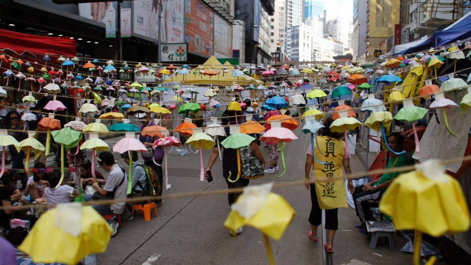 Protesters and people walk under hundreds of folded paper umbrellas at the occupied area in Causeway Bay, a shopping district of Hong Kong Thursday Oct. 30, 2014. Student democracy activists who have occupied Hong Kong streets for a month suggested Tuesday that direct negotiations with senior Chinese Communist Party officials could be a way to end their standoff with the local government. (AP Photo/Koji Ueda)