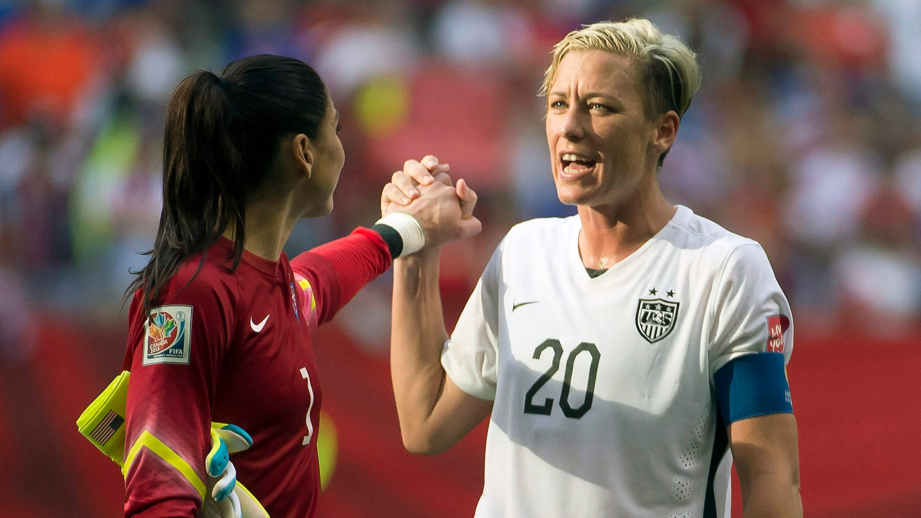 United States' Abby Wambach (20) celebrates her team's win with goal keeper Hope Solo following the second half of a FIFA Women's World Cup soccer match, Tuesday, June 16, 2015 in Vancouver, New Brunswick, Canada (Jonathan Hayward/The Canadian Press via AP) MANDATORY CREDIT