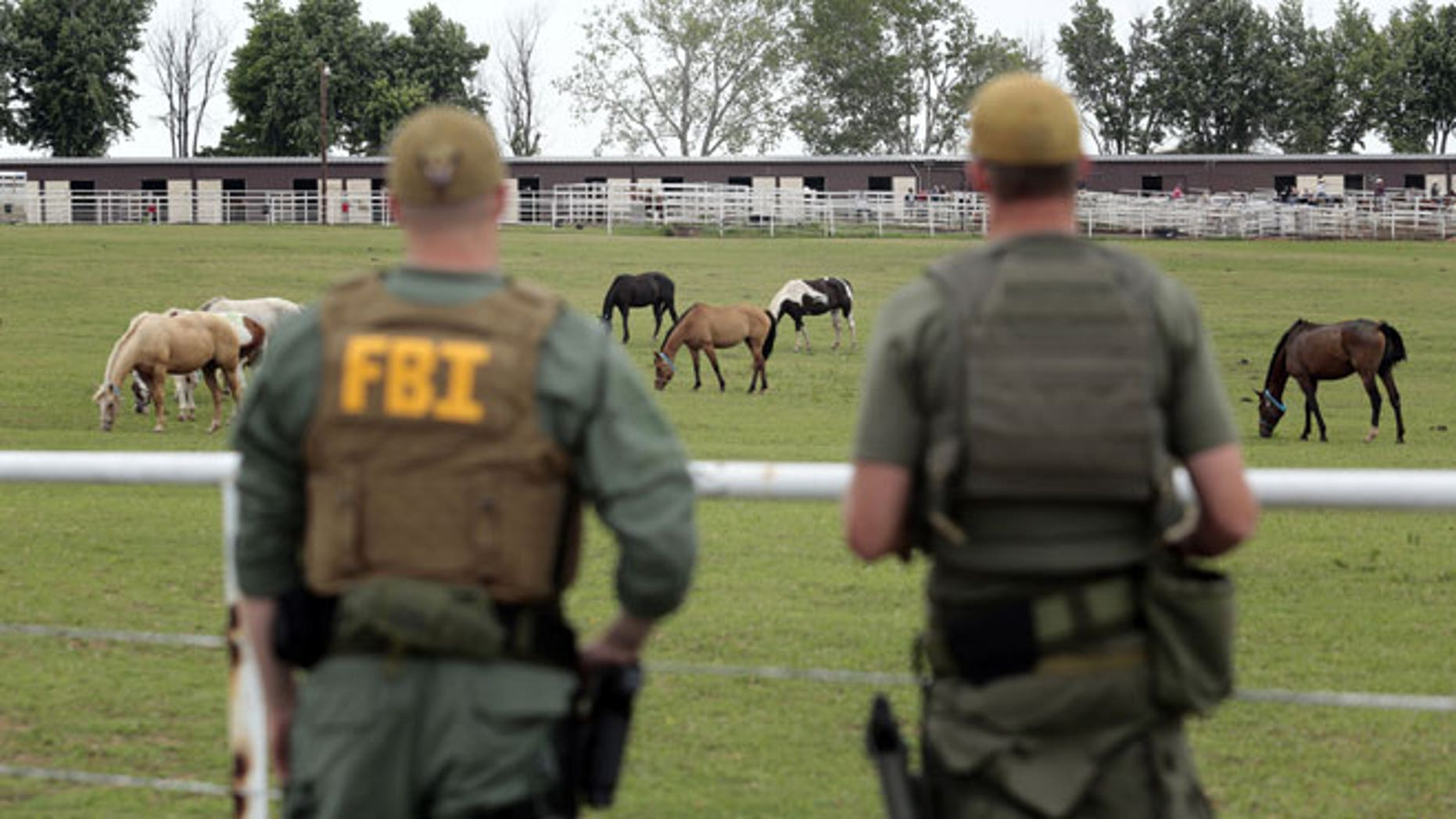 June 12, 2012: FBI agents overlook a horse ranch under investigation in Lexington, Okla. Federal agents raided the Oklahoma ranch and a prominent quarter horse track in New Mexico on Tuesday, alleging the brother of a high-ranking official in a Mexican drug cartel used a horse-breeding operation to launder money.