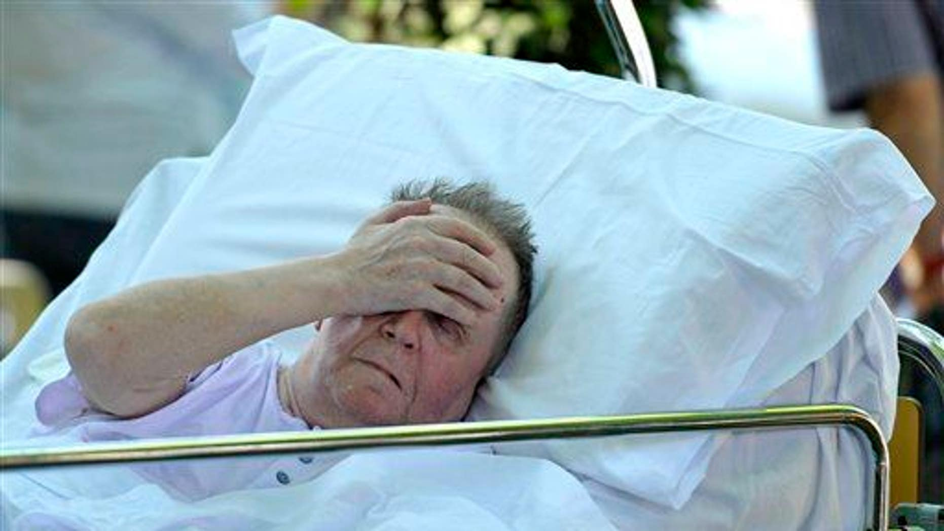 An elderly man lays on a bed in Mirandola, northern Italy, Tuesday, May 29, 2012.