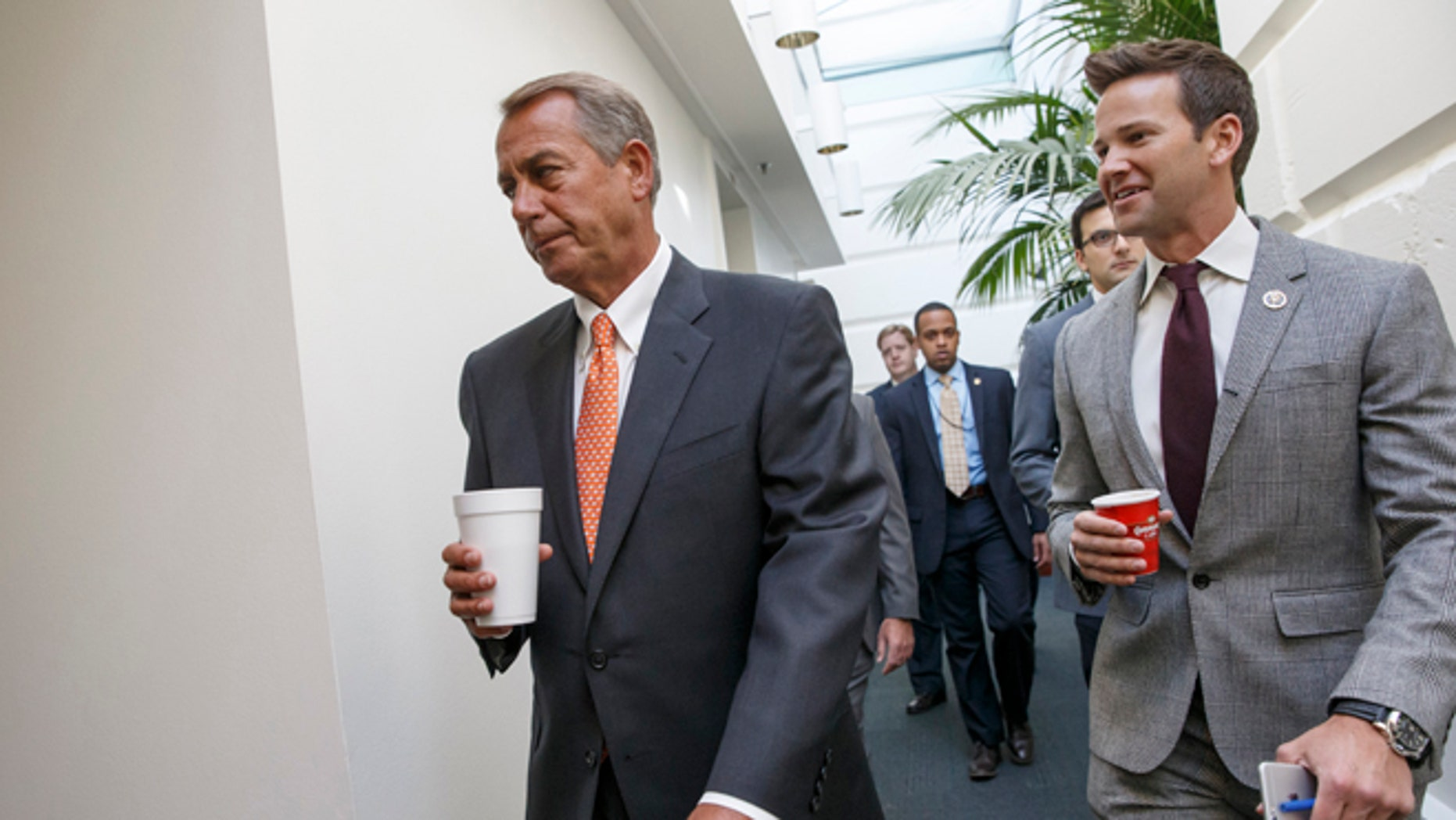 House Speaker John Boehner of Ohio walks with Rep. Aaron Schock, R-Ill., as House Republicans head to a closed-door meeting on thwarting President Barack Obama's executive actions on immigration by blocking the funding for the Department of Homeland Security. Friday, Jan. 9, 2015, on Capitol Hill in Washington. Obama's directives in November gave temporary relief from deportation to about 4 million immigrants in the country illegally, along with permits allowing them to work legally in the U.S. His move infuriated Republicans after their midterm election victories, and they vowed to retaliate once they assumed full control of Congress this week. (AP Photo/J. Scott Applewhite)
