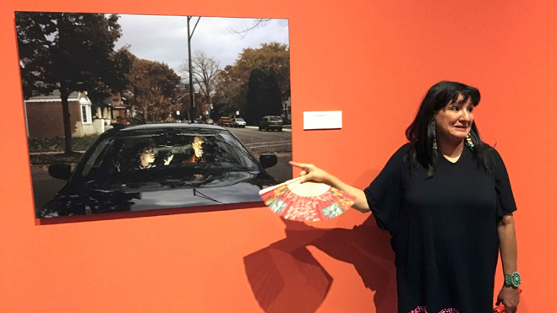 """This Wednesday, July 27, 2016 photo acclaimed Mexican-American author Sandra Cisneros points to a photograph by Cecil McDonald, Jr., at the National Hispanic Cultural Center in Albuquerque, N.M. at an exhibit based by her 1984 novel """"The House of Mango Street."""" The exhibit """"The House on Mango Street: Artists Interpret Community"""" features major themes of the novel of a Mexican-American girl coming of age in Chicago. (AP Photo/Russell Contreras)"""