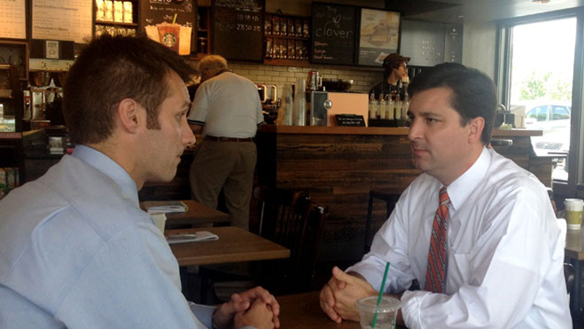 FILE: June 30, 2014: North Carolina Republican House candidate David Rouzer, right, talking with a campaign aide, in Raleigh, N.C.