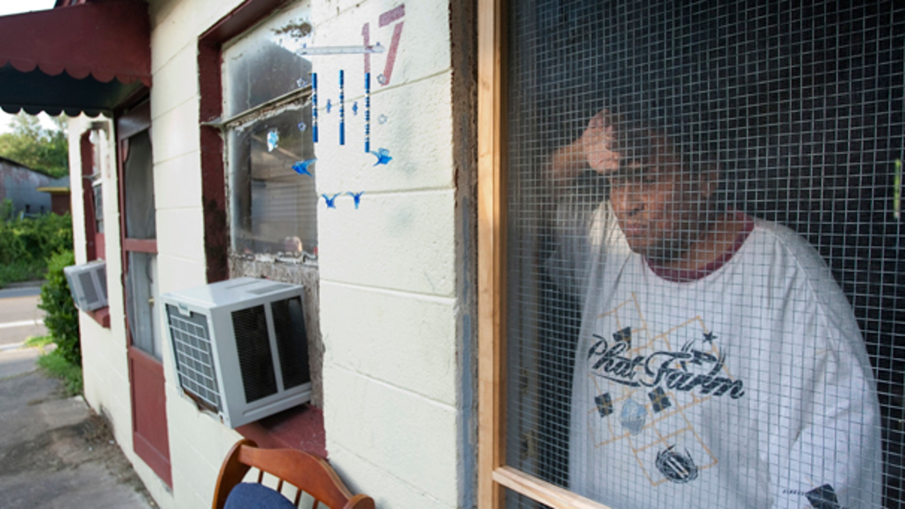 July 11: Tomas Rodriguez stands in his doorway next door to the apartment where Houston police say 34-year-old Alex Duncan is accused in the death of his visiting 6-year-old son after the boy allegedly was beaten for not falling asleep in Houston. (AP)