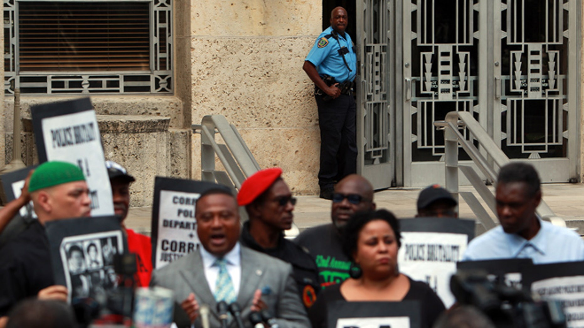 Sept. 25, 2012: An HPD officer peeks out of a door at City Hall as activists call for answers from city officials on why a police officer on Saturday fatally shot Brian Claunch outside City Hall in Houston.