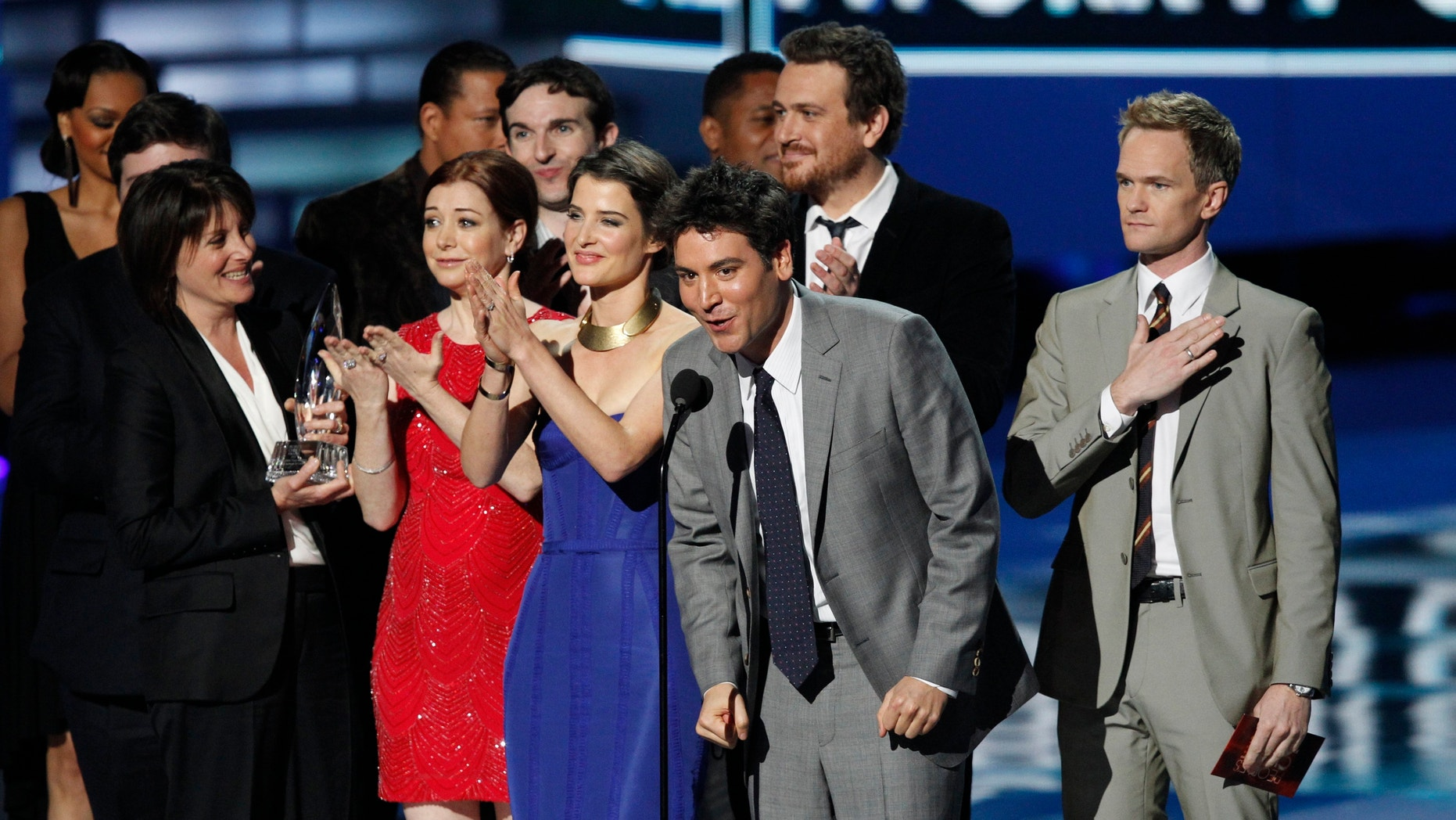 """Actor Josh Radnor, center, accepts the Favorite Network TV Comedy award for TV series """"How I Met Your Mother"""" at the 2012 People's Choice Awards in Los Angeles January 11, 2012."""