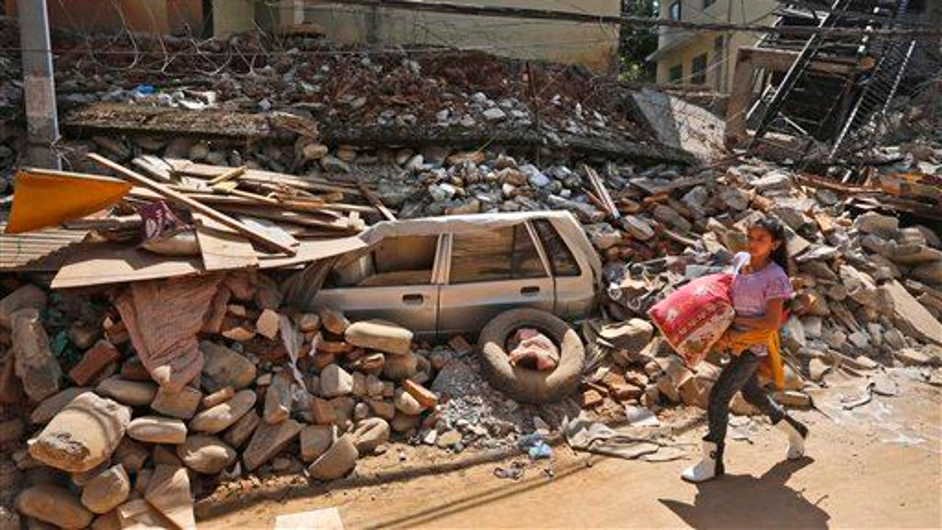 A Nepalese girl walks past a car, stuck in the debris of a damaged house, carrying a quilt received as relief material in Chautara, Sindhupalchok district, Nepal, Saturday, May 2, 2015.
