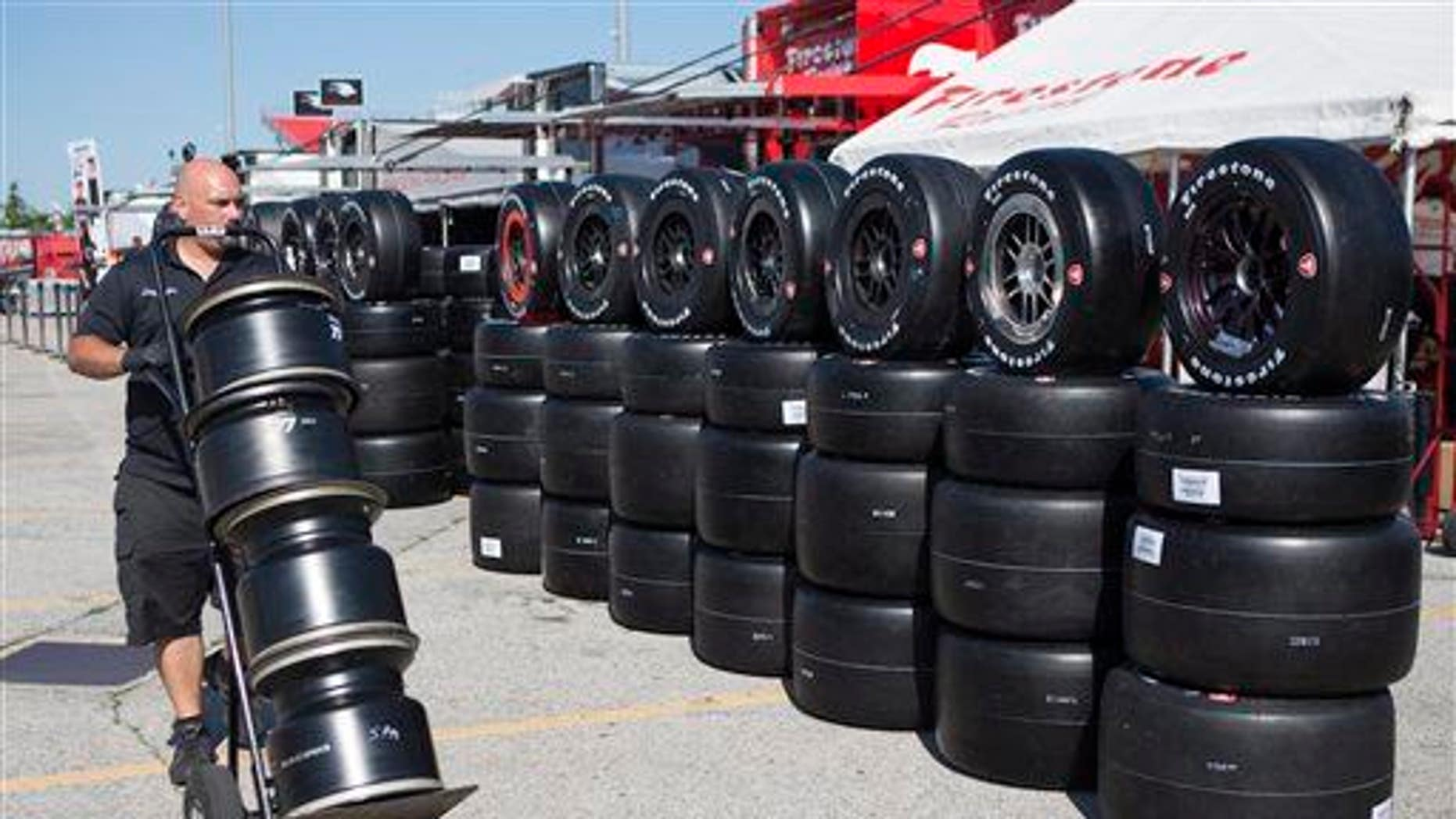 A technician carries rims to the Firestone Tires team as crews prepare for the Honda Indy Toronto IndyCar auto race in Toronto, Thursday, July 11, 2013.
