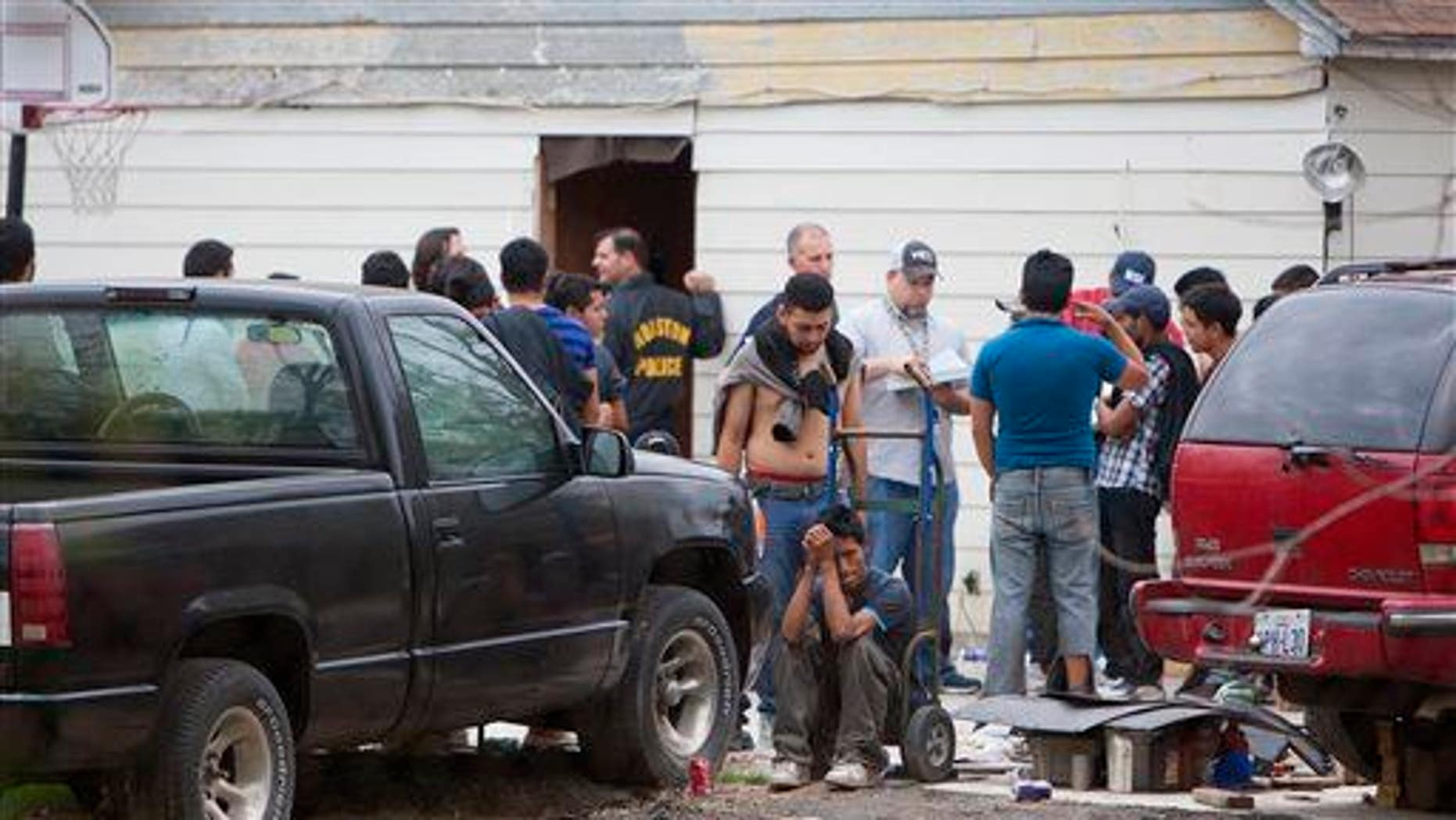 People wait outside a house, Wednesday, March 19, 2014, in southeast Houston.