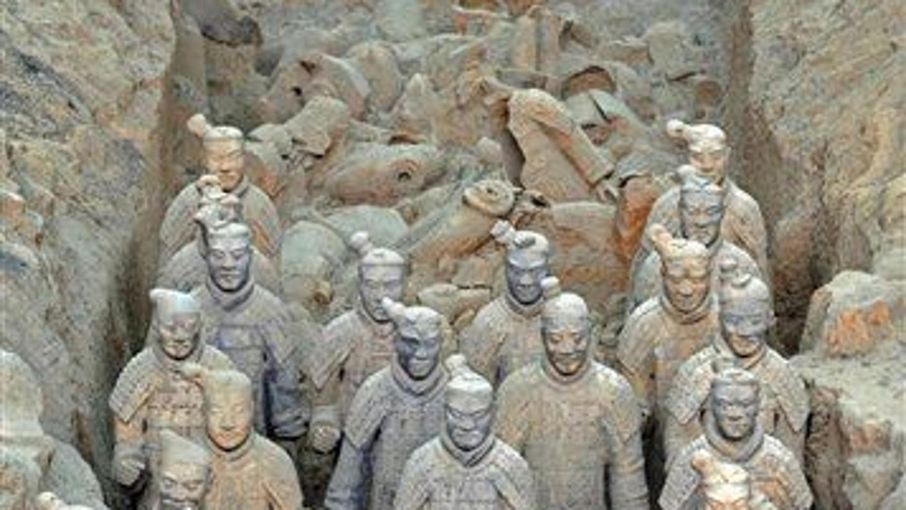 Life-sized sculptures of warriors stand upright in the pit where they were unearthed in 1974 in Xian, China, in this Oct. 16, 2004 file photo.