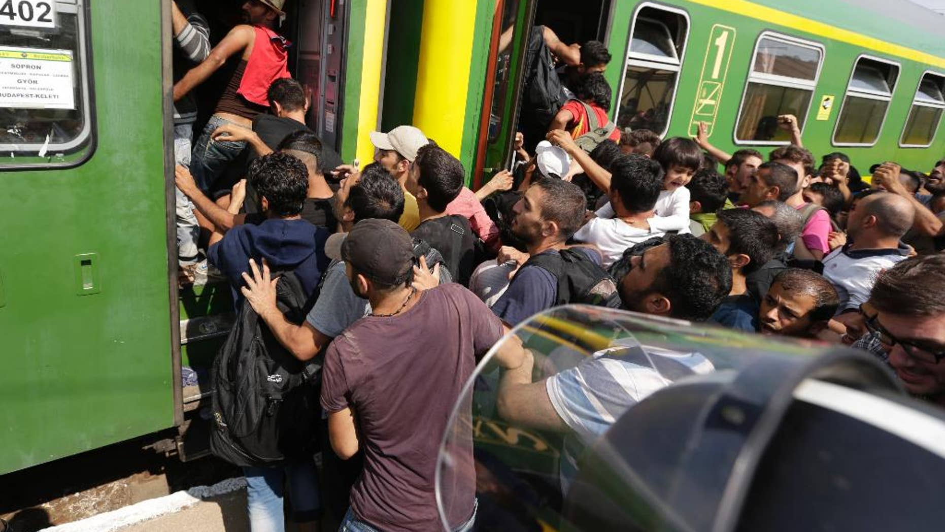 Migrants get back on a train in Bicske, Hungary, Thursday, Sept. 3, 2015. Over 150,000 migrants have reached Hungary this year, most coming through the southern border with Serbia. Many apply for asylum but quickly try to leave for richer EU countries. (AP Photo/Petr David Josek)