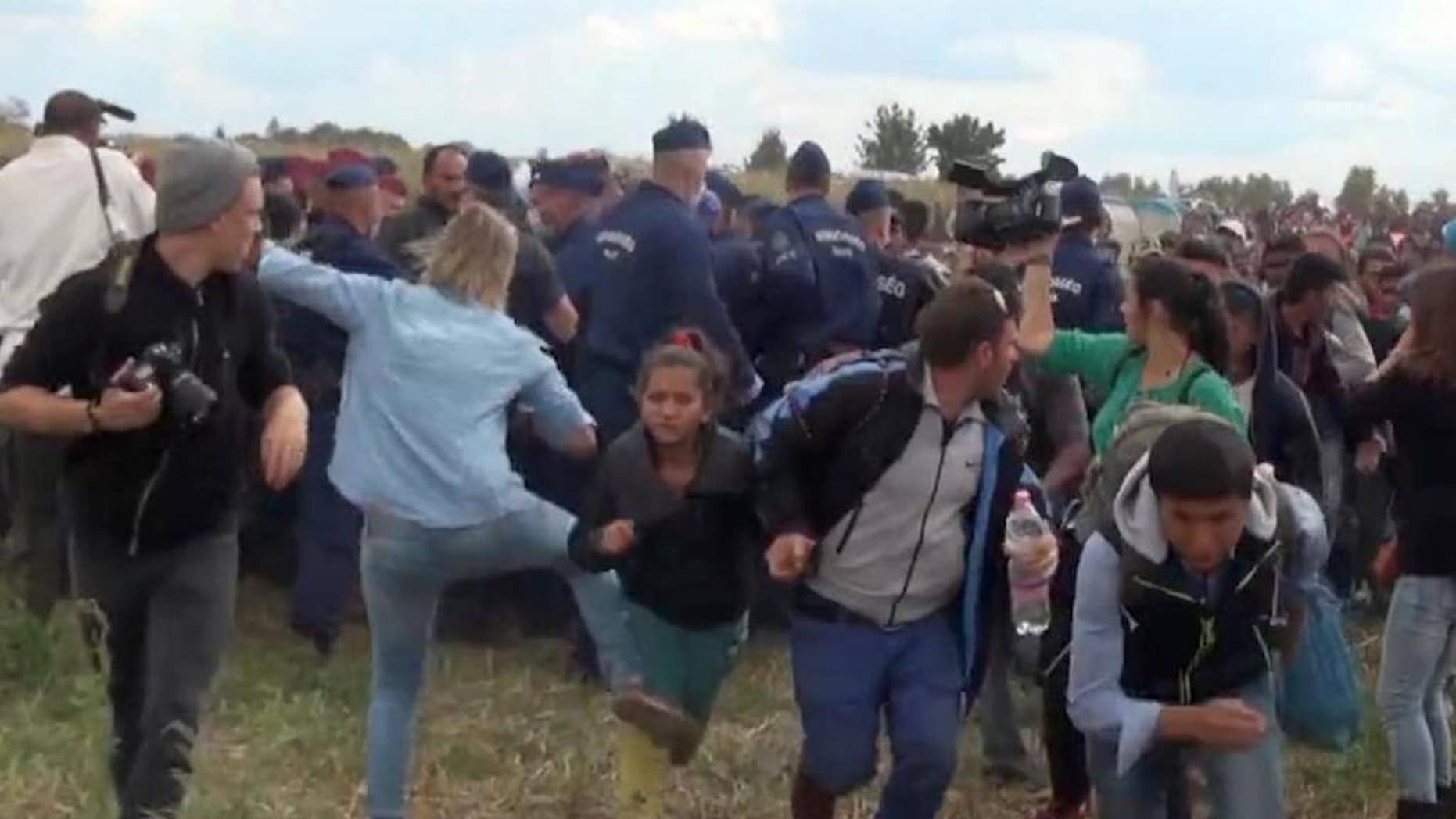 """In this image taken from TV a Hungarian camerawoman, center left in blue, kicks out at a young migrant who had just crossed the border from Serbia  near Roszke Hungary Tuesday Sept. 8, 2015. The camerawoman has been fired after she was caught on video kicking and tripping migrants entering Hungary across the border with Serbia. The N1TV Internet channel said their employee, widely identified in Hungarian media as Petra Laszlo, has been dismissed because she """"behaved unacceptably"""" at a makeshift gathering point where police take migrants immediately after they enter Hungary near the village of Roszke.(Index.Hu. via AP) HUNGARY OUT"""