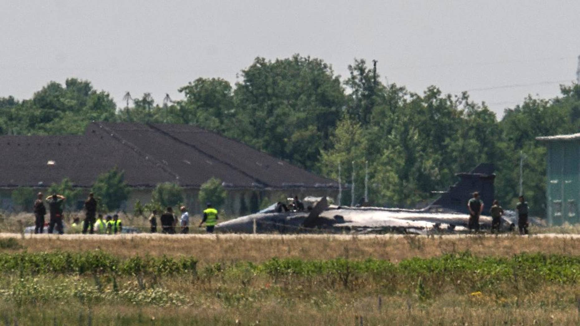 Military experts examine a JAS-39 C Gripen fighter jet of the Hungarian Defence Forces resting on the tarmac of the air base of Kecskemet, 85 kms southeast of Budapest, Hungary, after an emergency landing forced by a technical failure having occurred after take-off  Wednesday, June 10, 2015. The pilot catapulted successfully, he is currently kept under medical control. (Sandor Ujvari/MTI via AP)