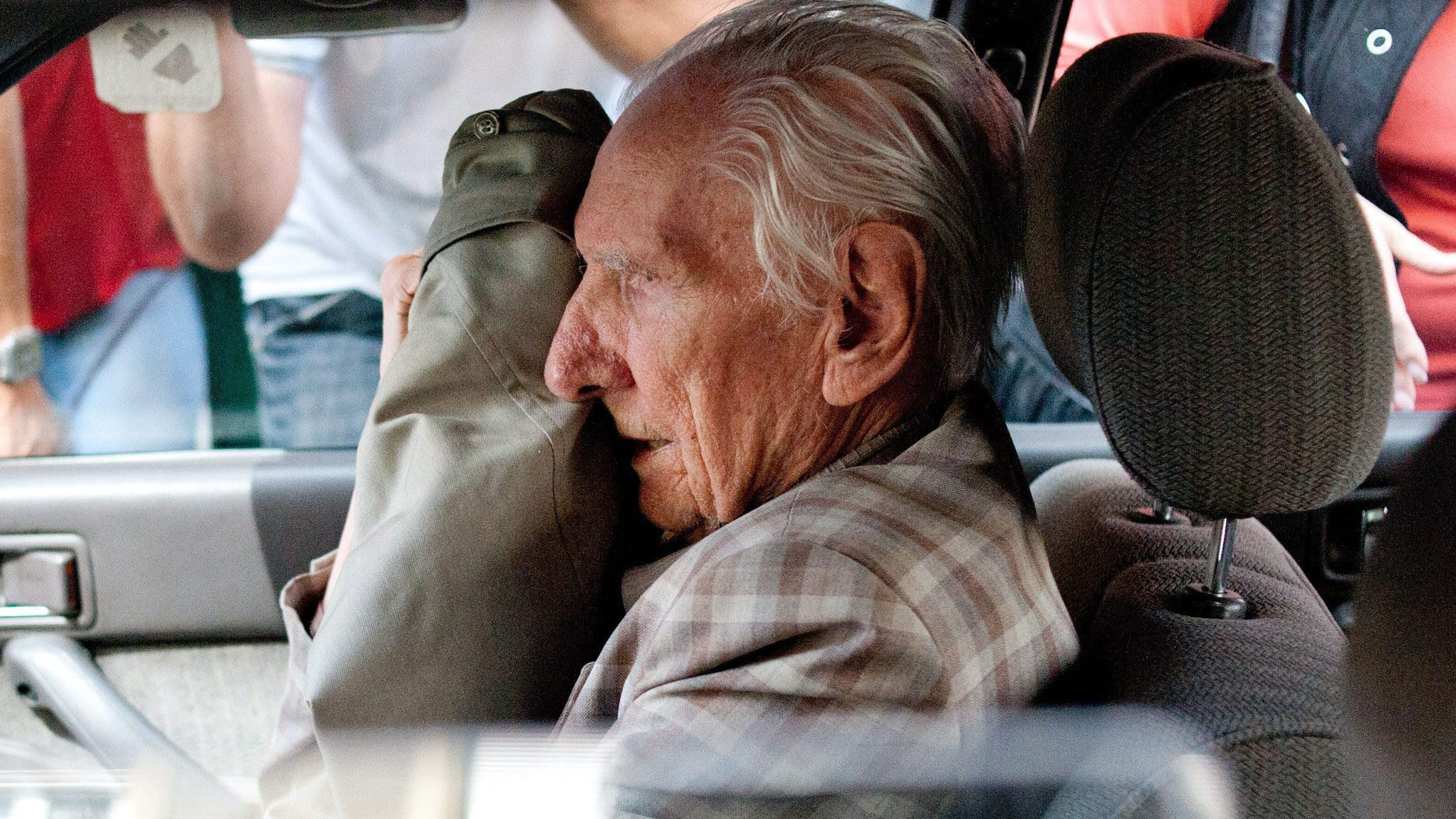 July 18, 2012 - FILE photo shows alleged Hungarian war criminal Laszlo Csatary covering his face in a car as he leaves the Budapest Prosecutor's Office after he was questioned by detectives on charges of war crimes during WWII and prosecutors ordered his house arrest in Budapest, Hungary. Csatary, a former police officer indicted in June 2013 by Hungarian authorities for abusing Jews and contributing to their deportation to Nazi death camps during World War II, has died.