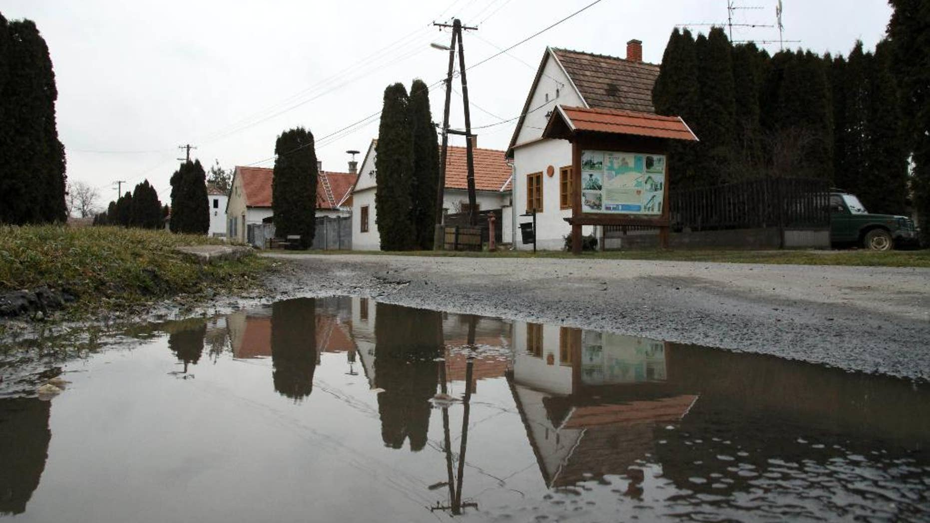 """FILE - In this Wednesday, Feb. 25, 2015 file photo, houses are reflected in a puddle on the main road in the village of Megyer, Veszprem county, 190 kilometers (120 miles) southwest of Budapest, Hungary. Rooms at Hungary's village-for-rent are going fast. Over 300 inquiries and reservations for 280 guests have been made since Mayor Kristof Pajer last week began advertising the village of Megyer, available for 210,000 forints ($760; 690 euros) a day. Pajer said Thursday, March 5, 2015,  tourists are coming from as far away as Australia, South Africa, Sweden and the United States and the village """"is booked solid in August and most of April and May."""" (AP Photo/MTI, Lajos Nagy, File)"""
