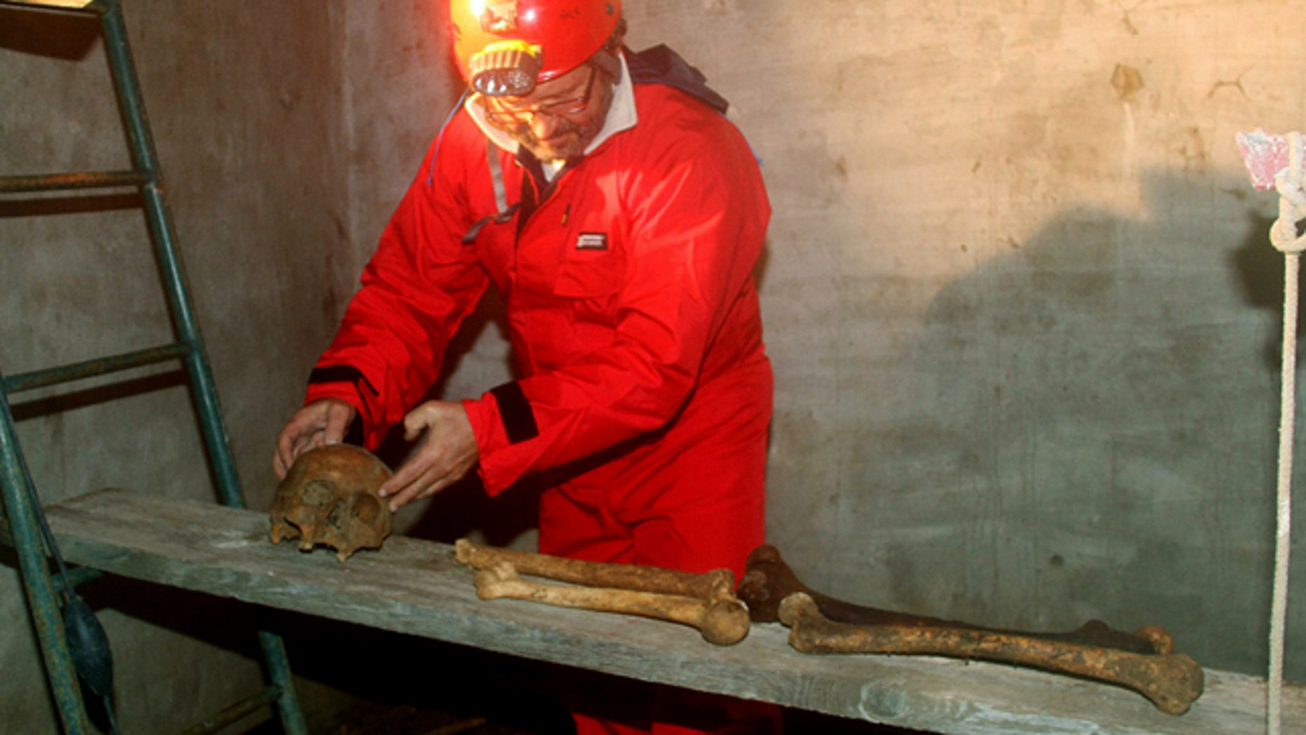 Italian researcher Antonio Moretti collects bones on a wooden board inside the crypt of San Sebastiano cemetery, in Porto Ercole, Italy. Moretti and a team of fellow scientists and academics want to solve the mystery surrounding the death of one of Italy's greatest artists: Caravaggio.