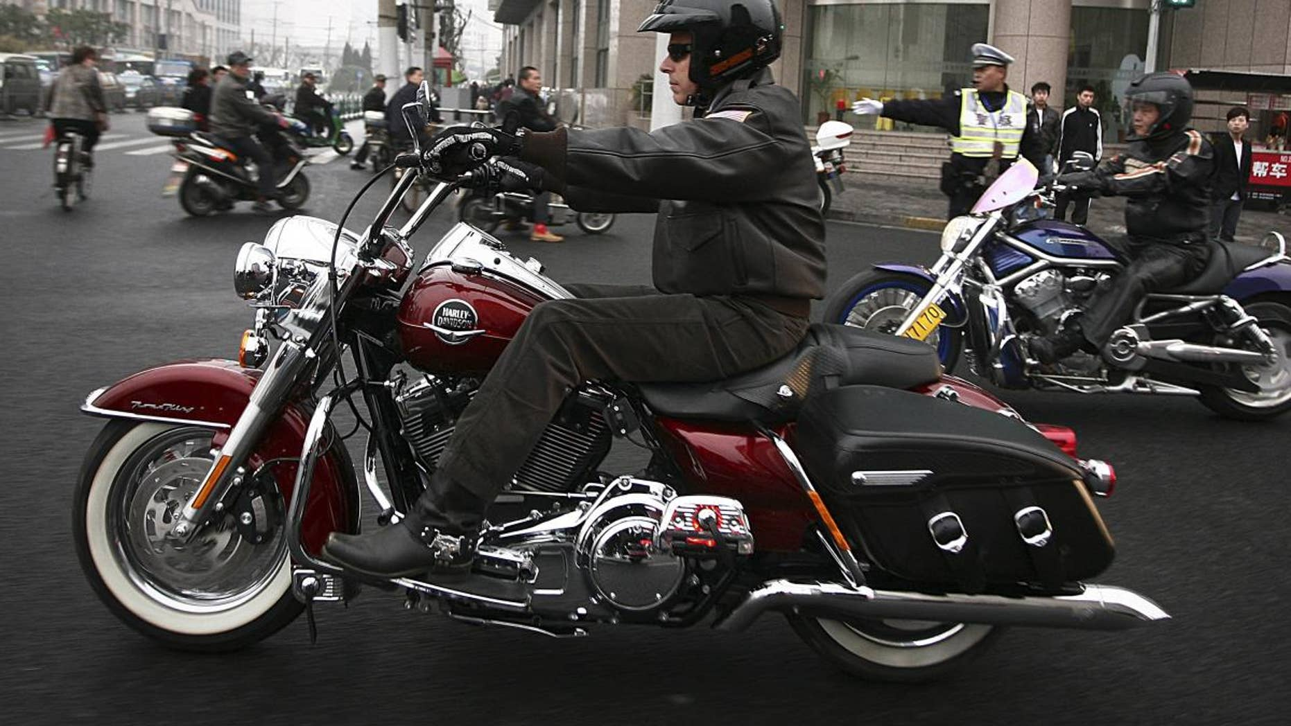 U.S. Ambassador to China Jon Huntsman rides a Harley-Davidson motorbike cruise around town in Shanghai, China Thursday April 7, 2011. Huntsman is in Shanghai to deliver a farewell speech at the Barnett-Oksenberg Lecture before heading back to U.S. later this month. (AP Photo)