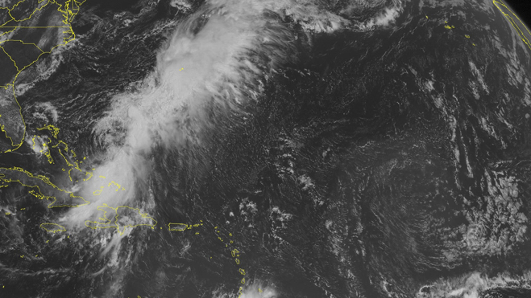 This NOAA satellite image taken Monday, Aug. 25, 2014, at 10:45 a.m. EDT shows Tropical Storm Cristobal affecting the southeastern Bahamas, far eastern Cuba and Hispaniola.  Most of the shower activity associated with the system was far-re moved from the center of circulation, indicating a sheared and possibly weakening system.  Meanwhile, widespread shower and thunderstorm activity was streaming to the northeast of the tropical system, along a stationary frontal boundary draped through the Atlantic.  A weak tropical wave was producing thunderstorms over the southern Lesser Antilles, as well. (AP Photo/Weather Underground)